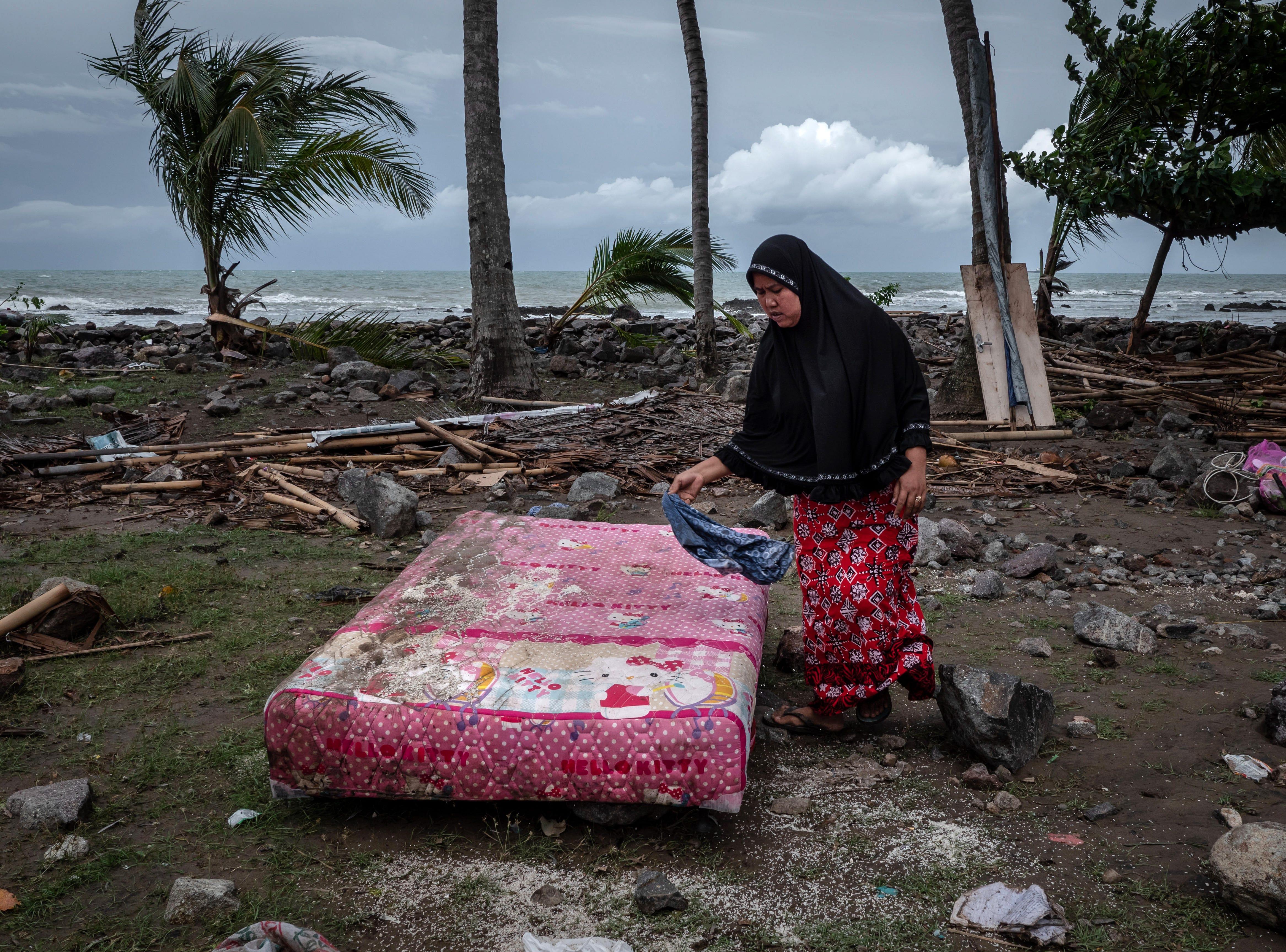 Una mujer busca sus pertenencias en sus casas destruidas después de ser golpeadas por un tsunami el 24 de diciembre de 2018 en Carita, provincia de Banten, Indonesia.