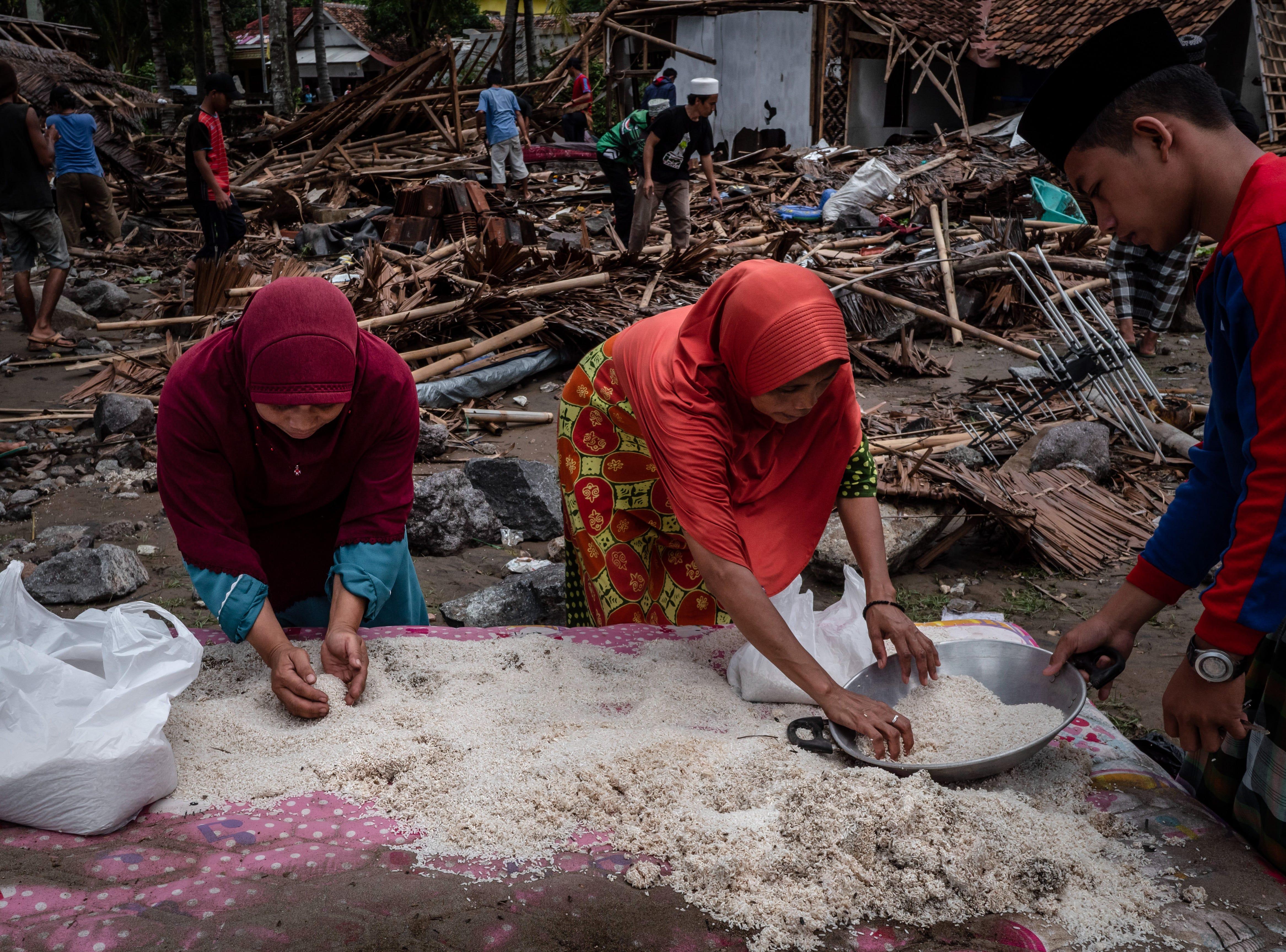 Mujeres recolectan arroz mientras aldeanos buscan sus pertenencias en sus casas destruidas después de haber sido golpeada por un tsunami el 24 de diciembre de 2018 en Carita, provincia de Banten, Indonesia.
