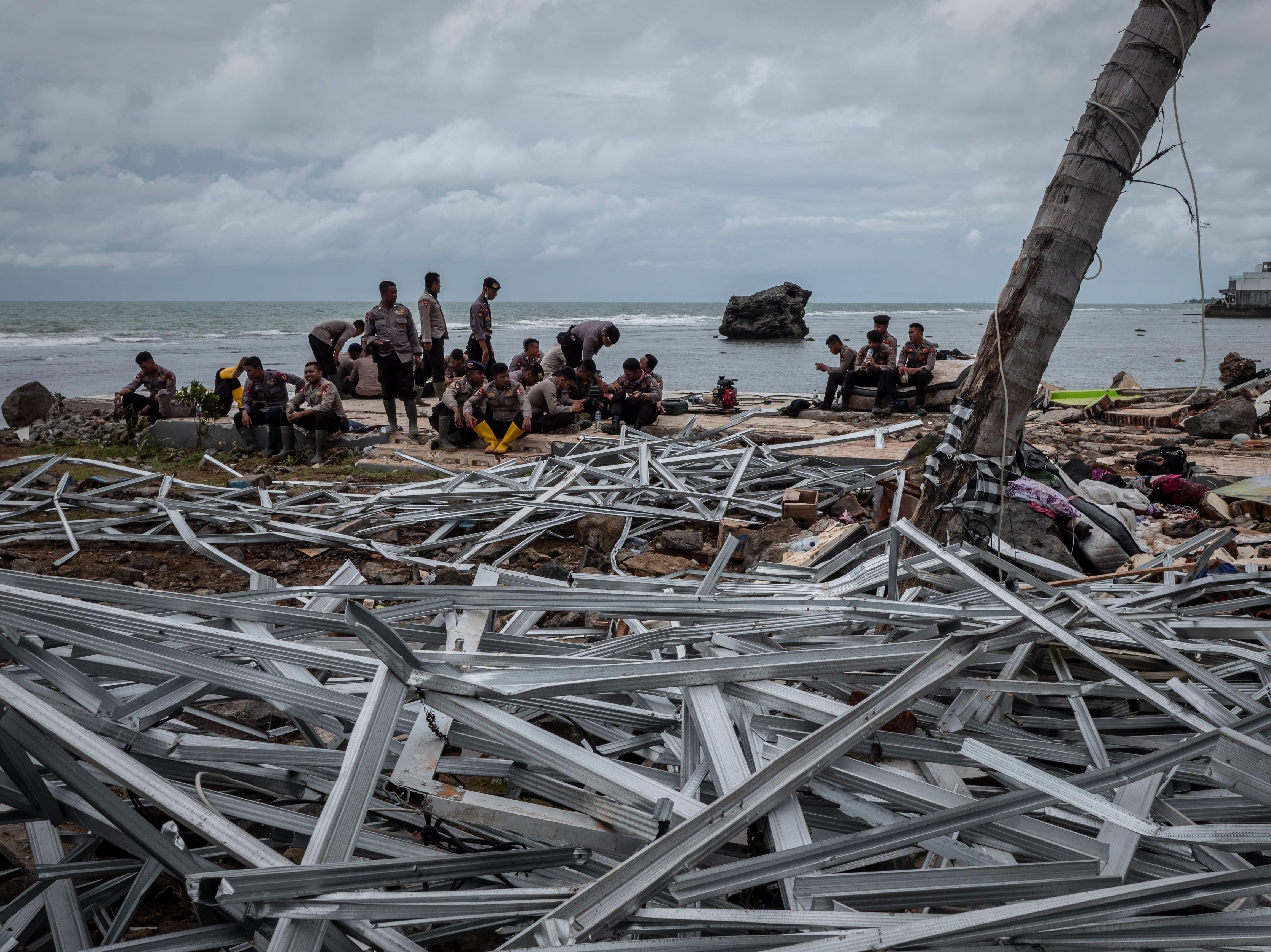 La policía de Indonesia descansa cerca de los escombros de un edificio luego de ser golpeado por un tsunami durante una búsqueda en un hotel resort el 24 de diciembre de 2018 en Carita, provincia de Banten, Indonesia.