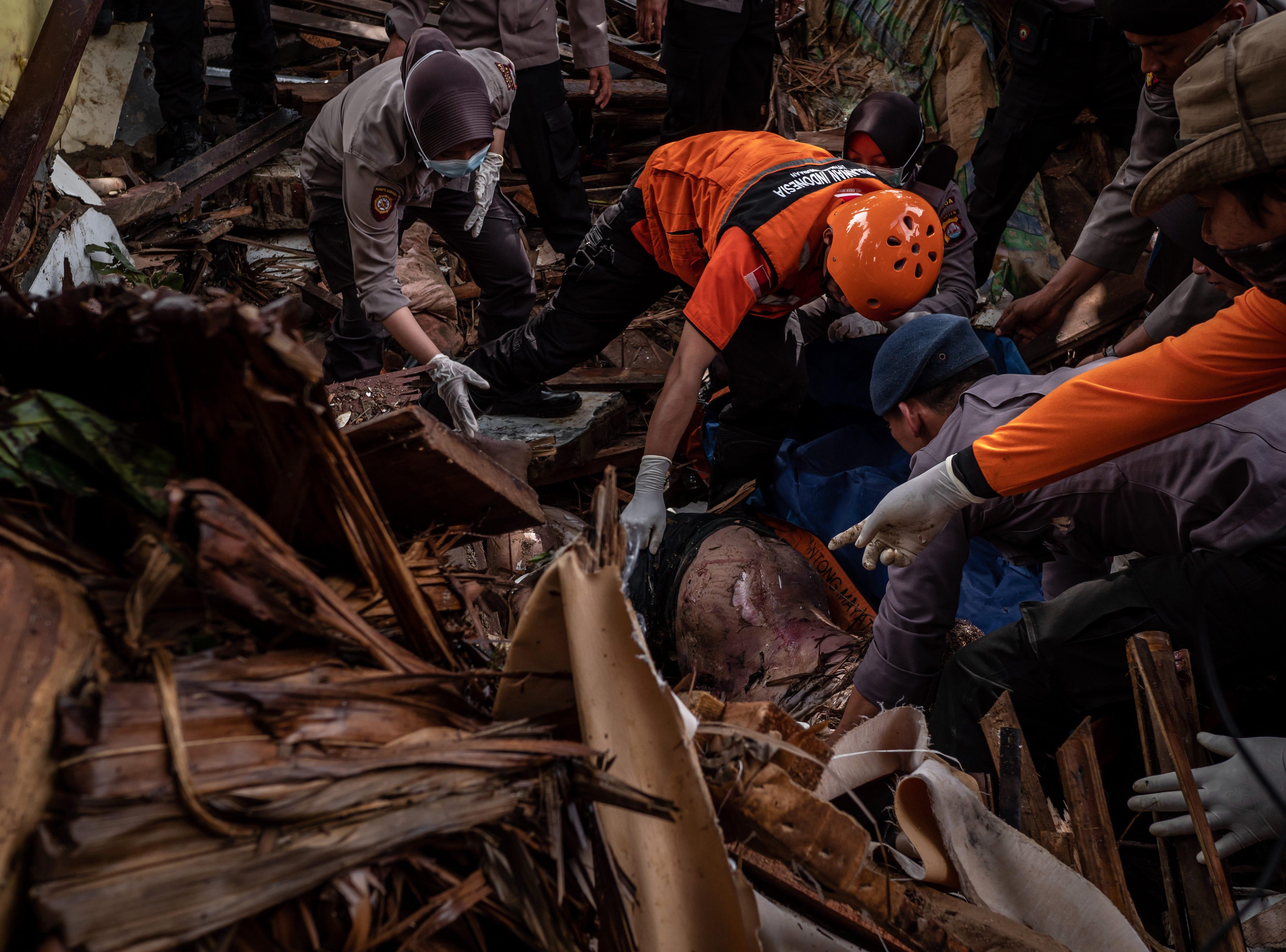Rescatistas recuperan el cuerpo de una víctima del tsunami durante una búsqueda en un hotel resort el 24 de diciembre de 2018 en Carita, provincia de Banten, Indonesia.