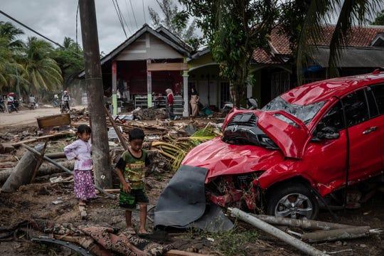 Dos niños pasan junto a un automóvil dañado tras el tsunami del 24 de diciembre de 2018 en Carita, provincia de Banten, Indonesia.