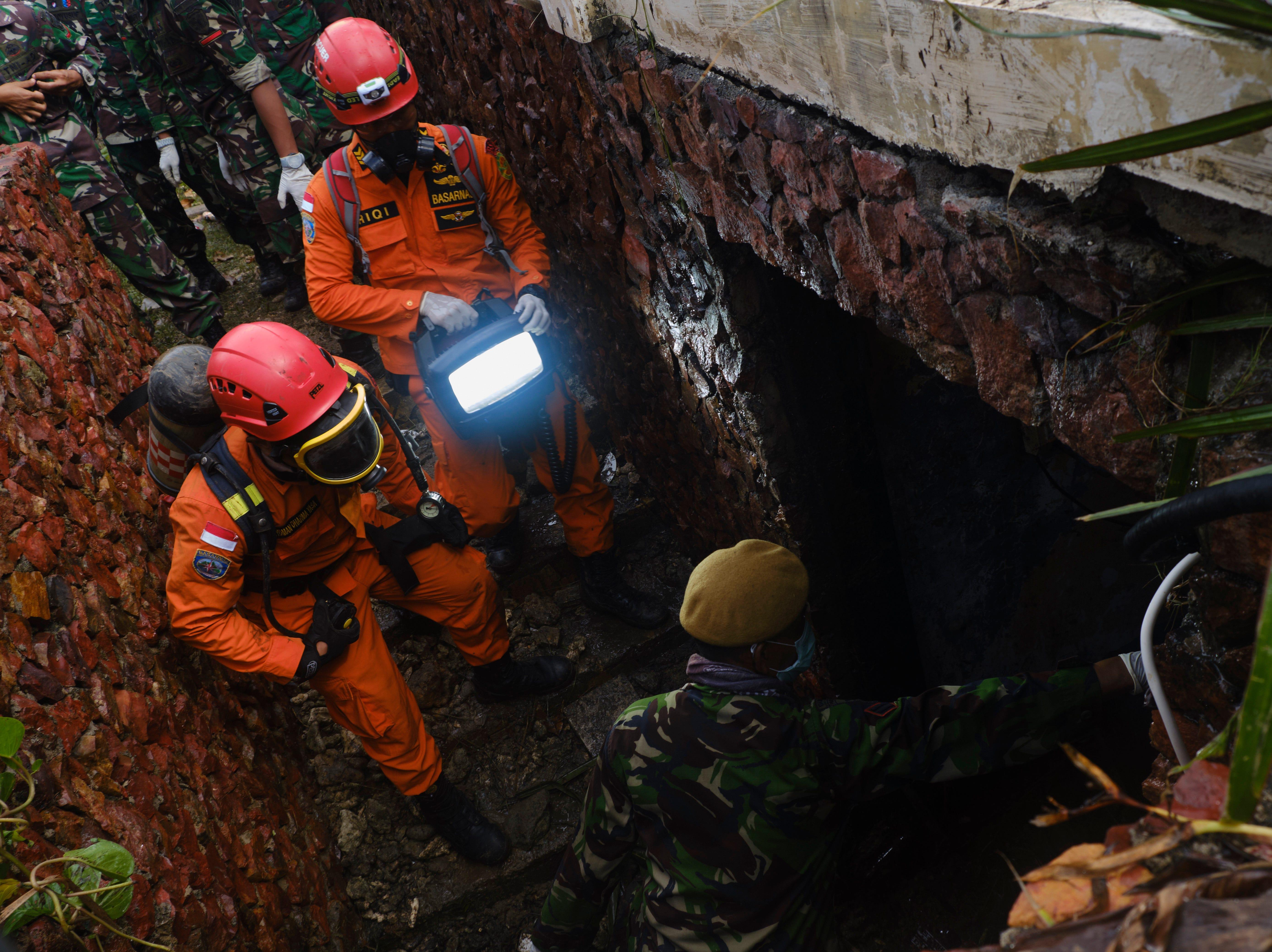 Los trabajadores de rescate se preparan para buscar en un espacio subterráneo víctimas del tsunami en un hotel resort el 24 de diciembre de 2018 en Tanjung Lesung, Indonesia.