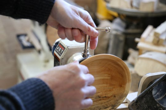 Edward Bryan attaches a bowl he turned into his lathe for polishing on December 20, 2018.