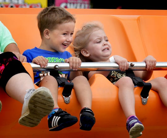 Vivian Henry, of Dover Township, and Jakob Koch, of Manchester Township, both 3, have unique reactions to their ride on the Happy Swing at the York Fair children's midway Friday, Sept. 14, 2018. The fair continues through Sunday, Sept. 16. Bill Kalina photo