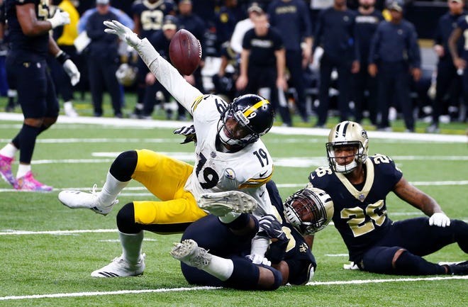 Pittsburgh Steelers wide receiver JuJu Smith-Schuster (19) fumbles the ball as New Orleans Saints defensive tackle Sheldon Rankins tackles him, causing a turnover in the final minute of the second half of an NFL football game in New Orleans, Sunday, Dec. 23, 2018. The Saints won 31-28, clinching the top seed for the NFC and home field advantage for the playoffs. (AP Photo/Butch Dill)
