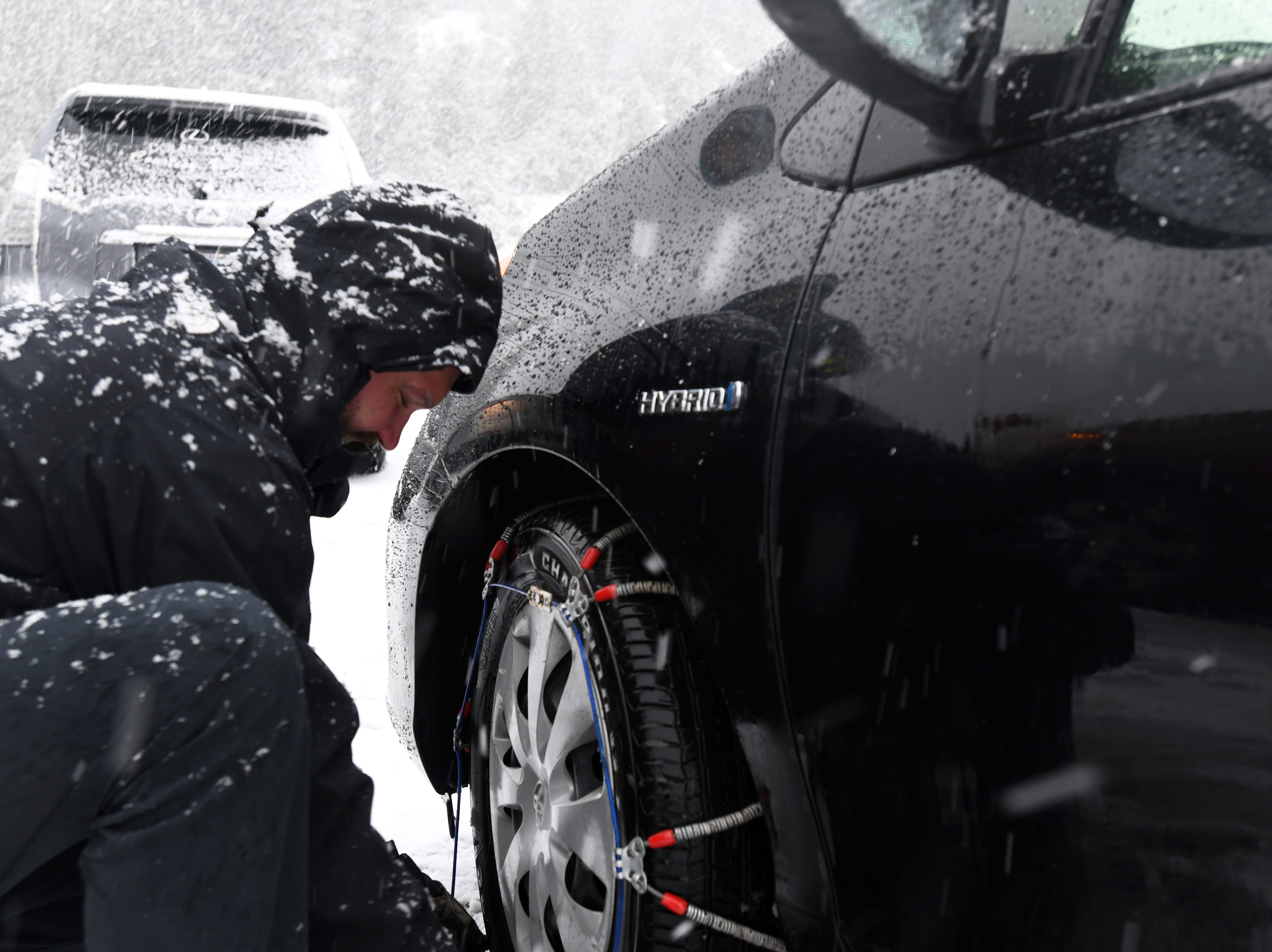 Tim Brink, 43, installs tire chains on his car as heavy snow falls on the Mt. Rose Highway on Christmas Eve 2018.