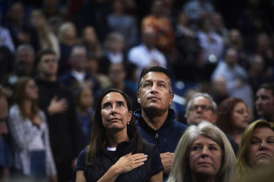 Nevada Governor Brian Sandoval and First Lady Lauralyn McCarthy stand at attention during the singing of the National Anthem at a Wolf Pack basketball game on Dec. 15, 2018.