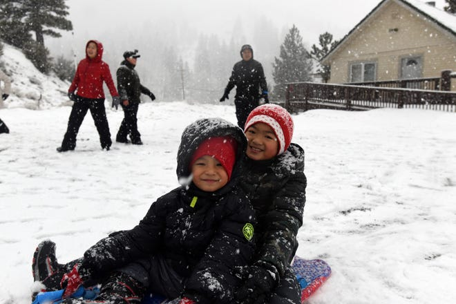 Brandon Nguyen and Lam Pham play in fresh snowfall near the Sky Tavern Ski Area off the Mt. Rose Highway on Dec. 24, 2018.