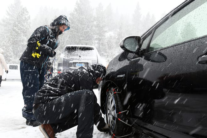 Tim Brink, 43, and Laetitia Brink, 40, install tire chains on their car as snow falls on the Mt. Rose Highway on Christmas Eve, 2018.