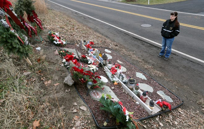 Lisa Entz stops at the memorial remembering fallen West Webster firefighters Tomasz Kaczowka and Mike Chiapperini. Both were shot and killed six years ago while responding to a house fire on Lake Road.  Entz was an  active West Webster firefighter on that day.