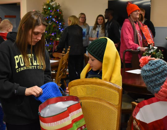 A woman and her son look through their gifts donated by Viviane Mukangamije at the Simonka Place in Keizer on Dec. 23, 2018.