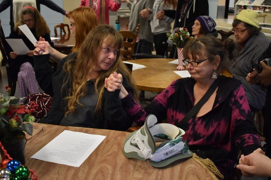 """Two women join hands while singing """"We are the World"""" at the Simonka Place in Keizer on Dec. 23, 2018."""
