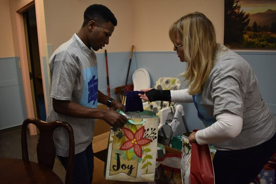 Joshua Nziyunkira, 39, and Debby Doyle, 60, help unload the donations organized by Viviane Mukangamije for the women and children at the Simonka Place in Keizer on Dec. 23, 2018.