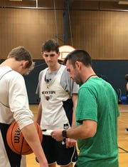Stayton center Kaleb Anundi (center) listens to instructions from coach Joe Kiser (right) during practice at Stayton High School on Dec. 21, 2018.