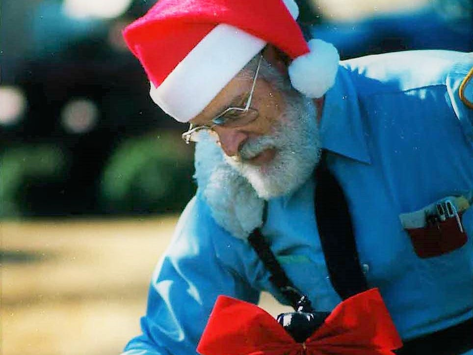 """Postal carrier Robert Holtz makes a delivery to an ornate mailbox on South Jefferson Street on Dec. 20, 1985. Holtz received his seasonal headgear from his wife and wore it on his rounds. He said he usually grows a beard during an annual fall elk hunt and has been urged to play Santa because of the beard's color. Holtz made his rounds whistling """"Jingle Bells"""" saying he wanted to get into the spirit of the season."""