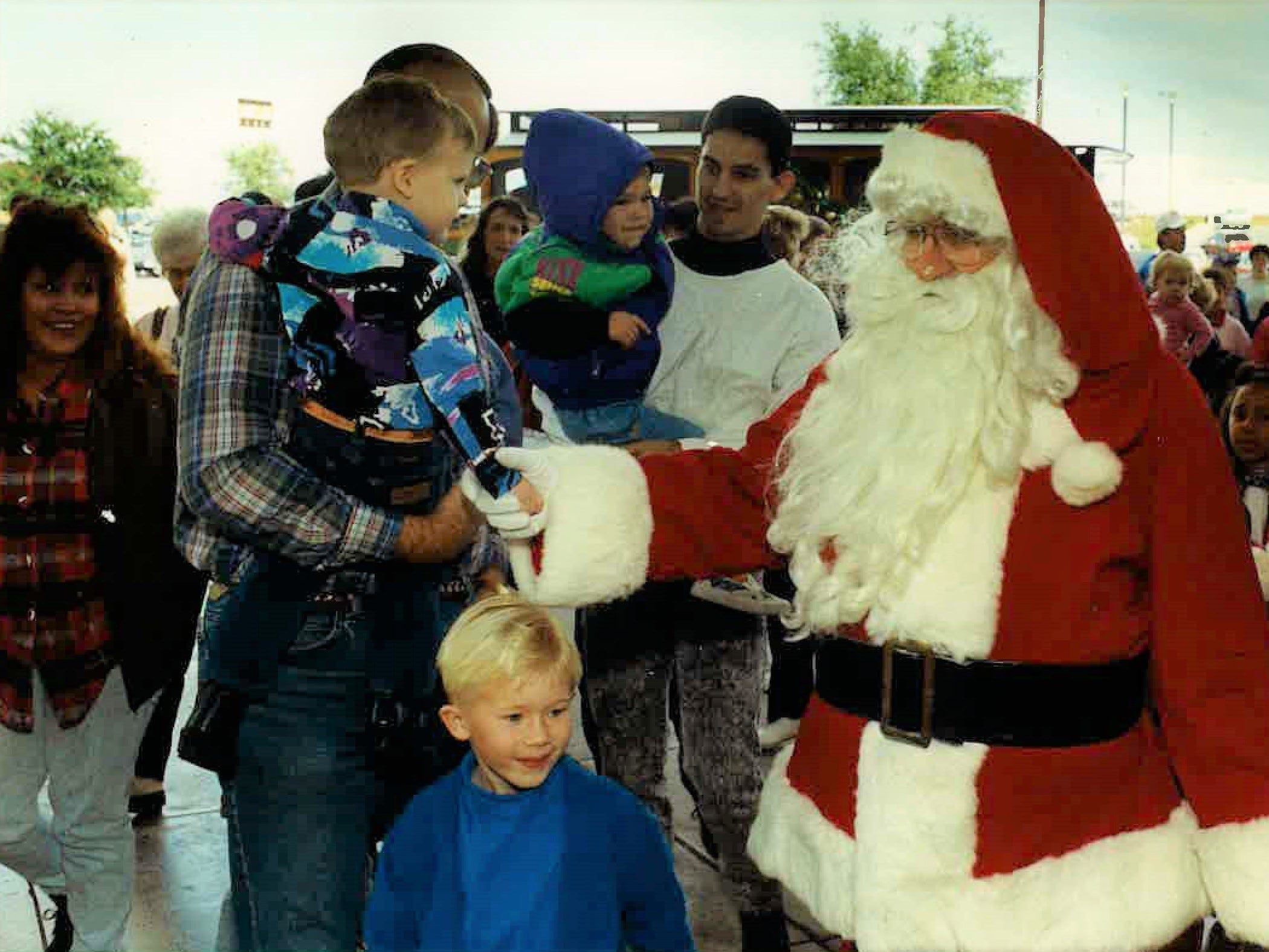Santa arrives at Sunset Mall greeting youngsters, including Taylor Cox of Midland (front), just outside after getting off of the Trolley-Bus with a group of children in 1992.