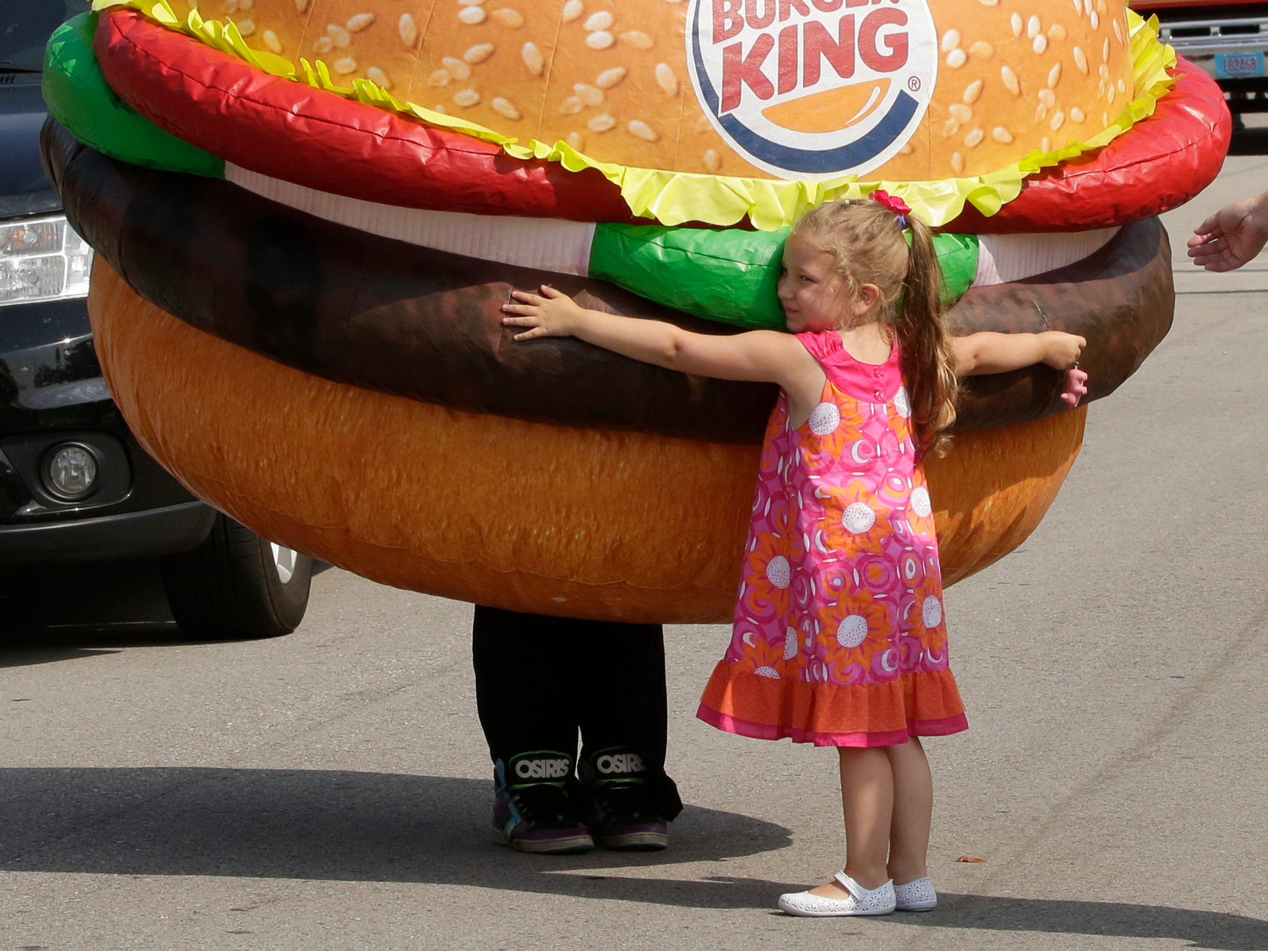 Winsley Schoen, 4, hugs a burger character during Brat Days, Saturday, August 4, 2018, in Sheboygan, Wis.