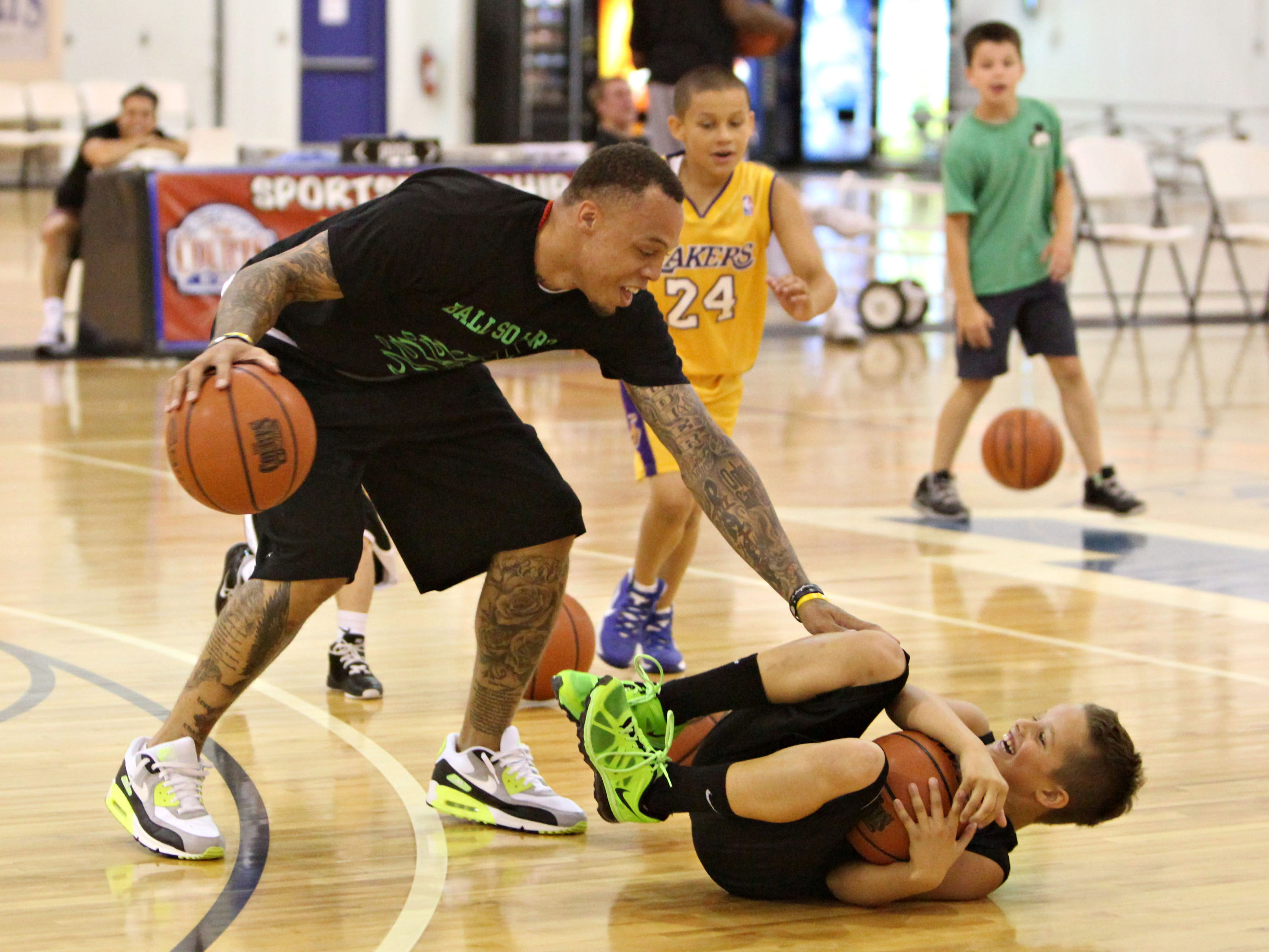 Former Bear Deven Mitchell tags Cooper Roy, 9, during a kids camp at The Courts on Monday, July 1, 2013.