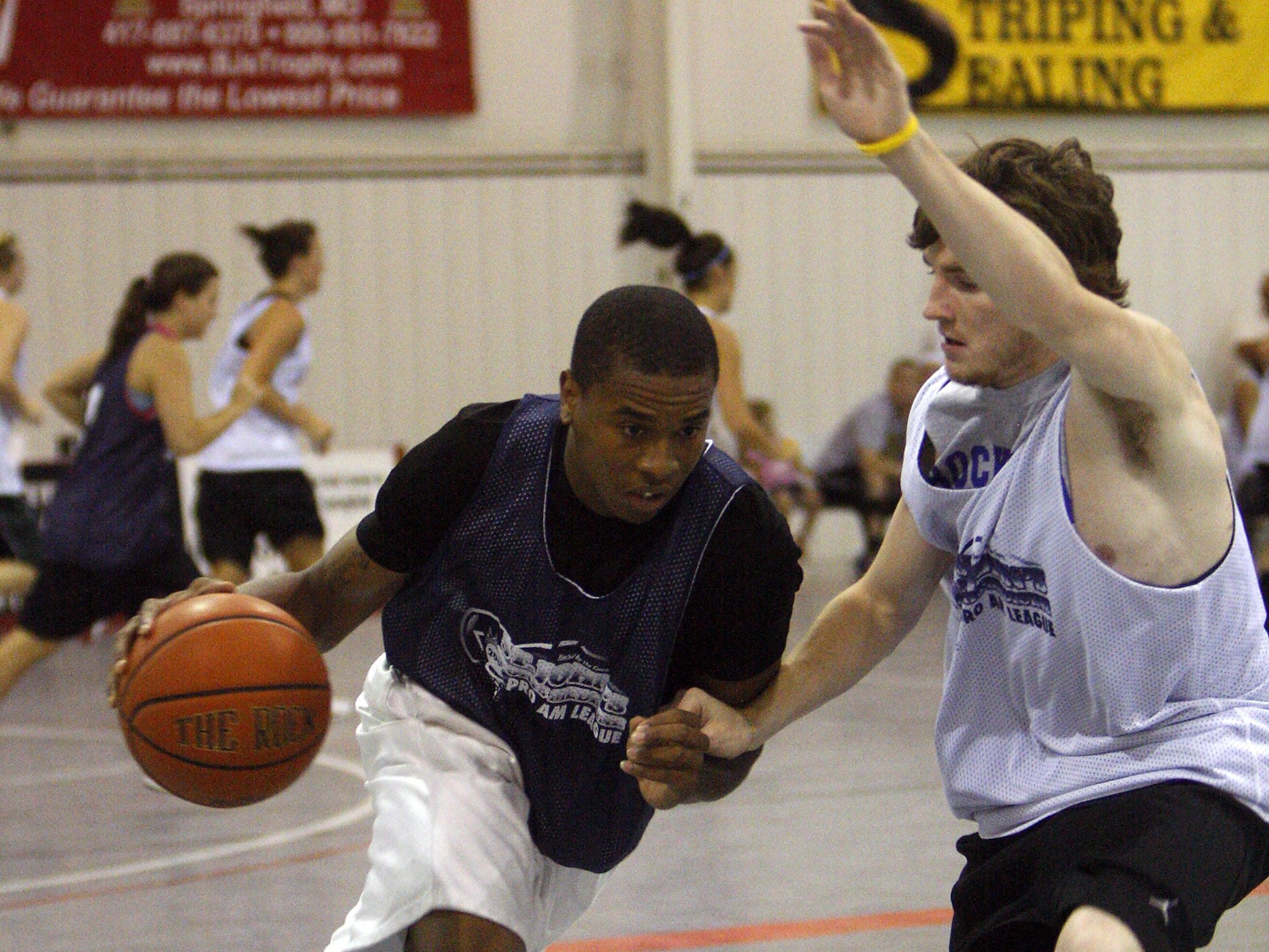 Team Osos forward Keith Pickens, left, drives along the baseline with the basketball while defended by Team Crusaders guard Jayme Donnelly, right, during their basketball game at the St. John's Sports Medicine Pro Am League 2009 hosted by The Courts in Springfield, Missouri, Wednesday, July 1, 2009.