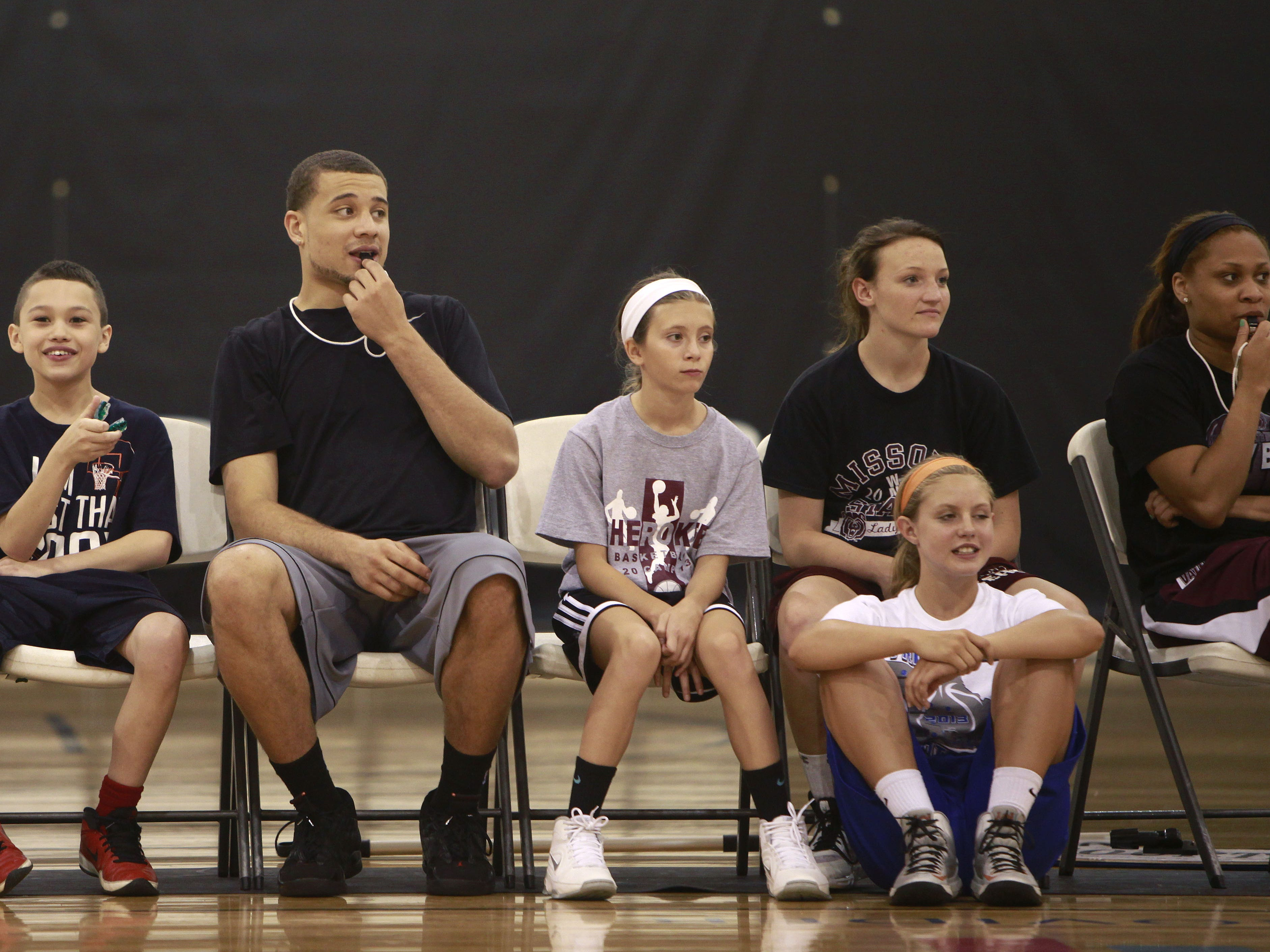 Former Missouri State basketball player Kyle Weems sits on the bench with kids in his basketball camp at The Courts on Tuesday, June 25, 2013.