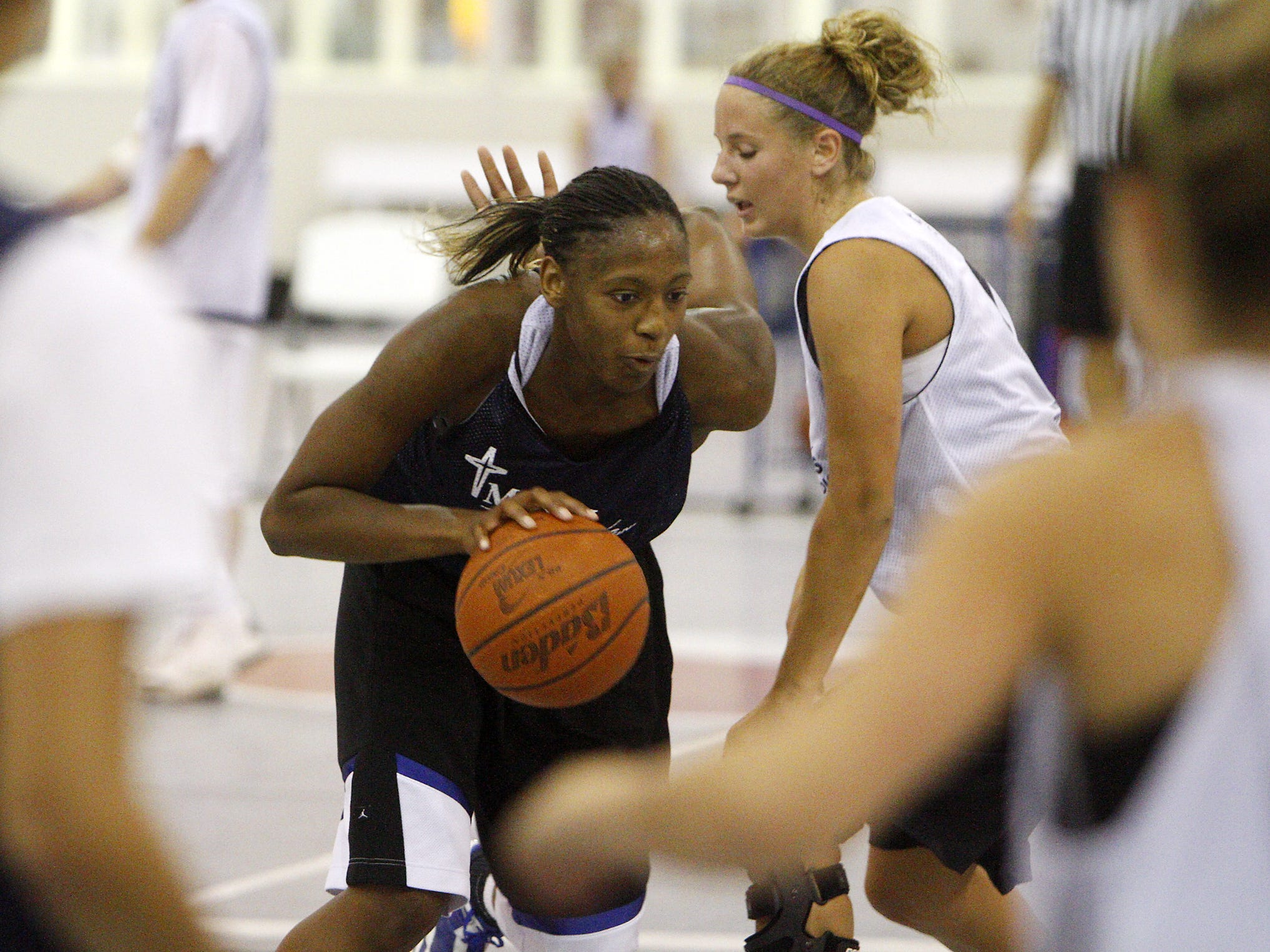 Tia Mays, left center, drives with the basketball during a game at the The Courts in Springfield, Missouri, Thursday, July 8, 2010.