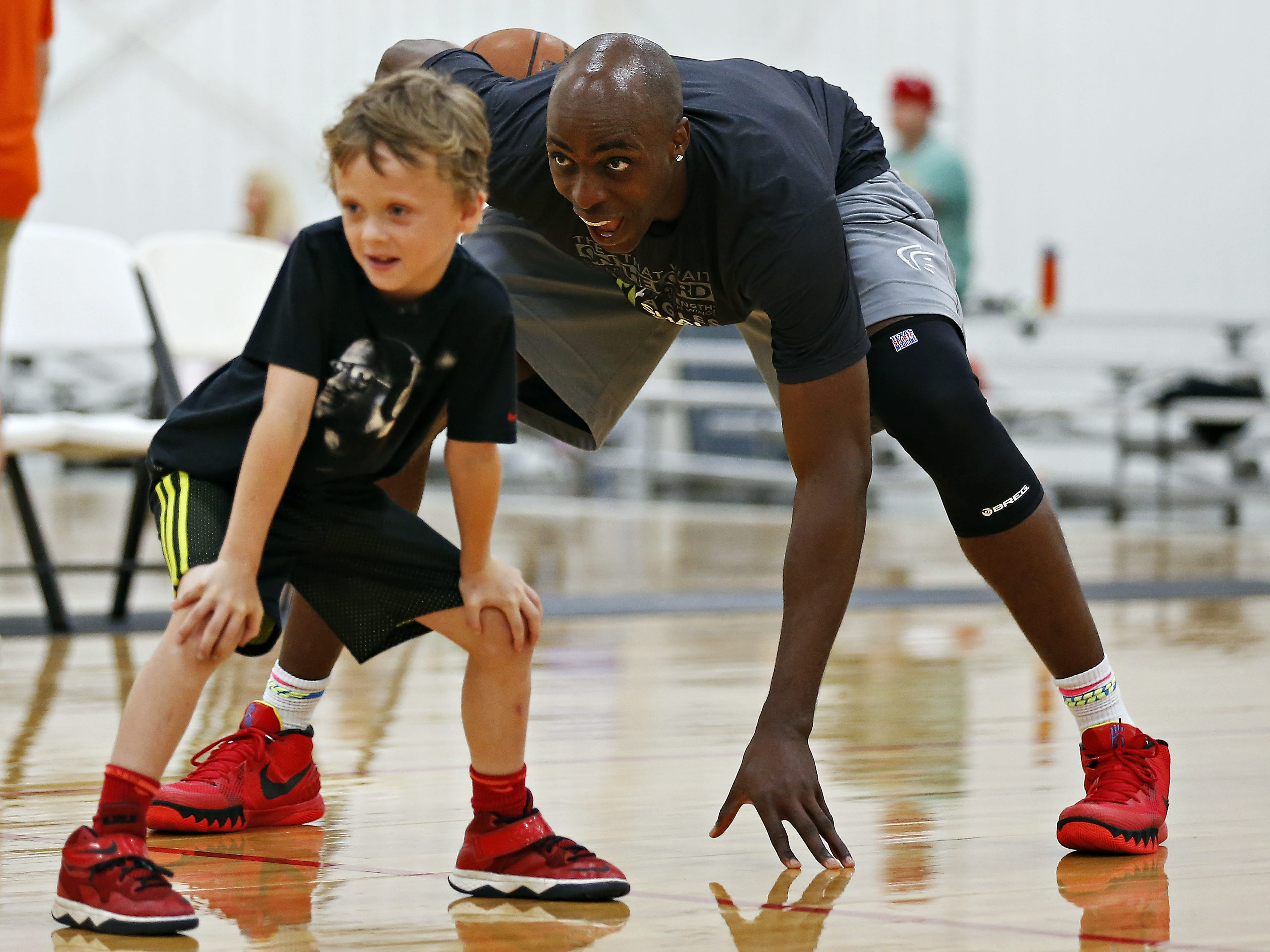 Springfield native and NBA player Anthony Tolliver plays with one of the children attending his annual basketball camp at the E-Zone basketball courts in Springfield, Mo. on June 16, 2015.