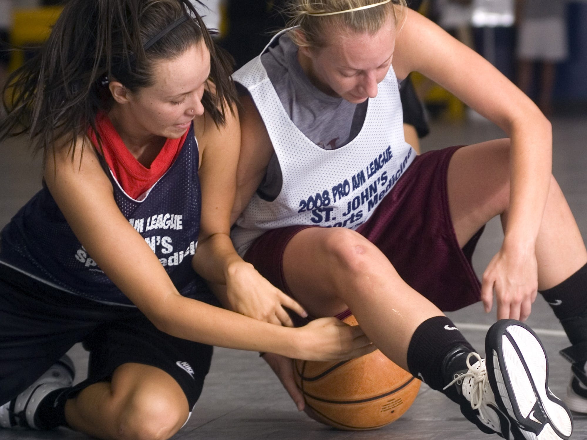 Lady Crusaders guard Kelsie Hargus, right, and Bank of Bolivar guard Jessica Pickett, left, fall to the hardwood and right for control of the basketball during the secod half of their The Courts College Pro-Am basketball game at The Courts in Springfield, Missouri, Wednesday, July 2, 2008.