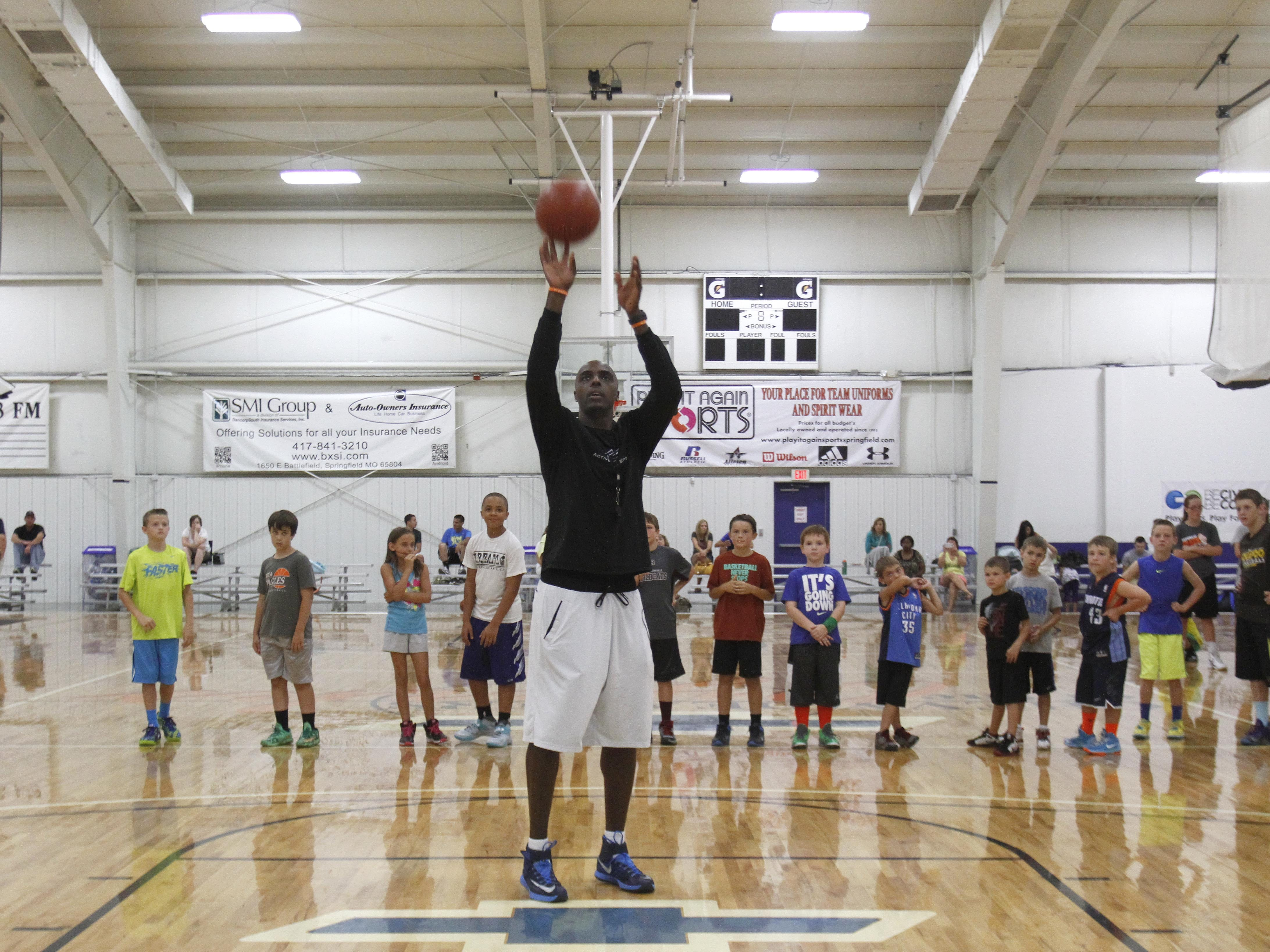 Phoenix Suns basketball player Anthony Tolliver shoots a basket as kids look on during his basketball camp at The Courts on Tuesday, July 22, 2014.