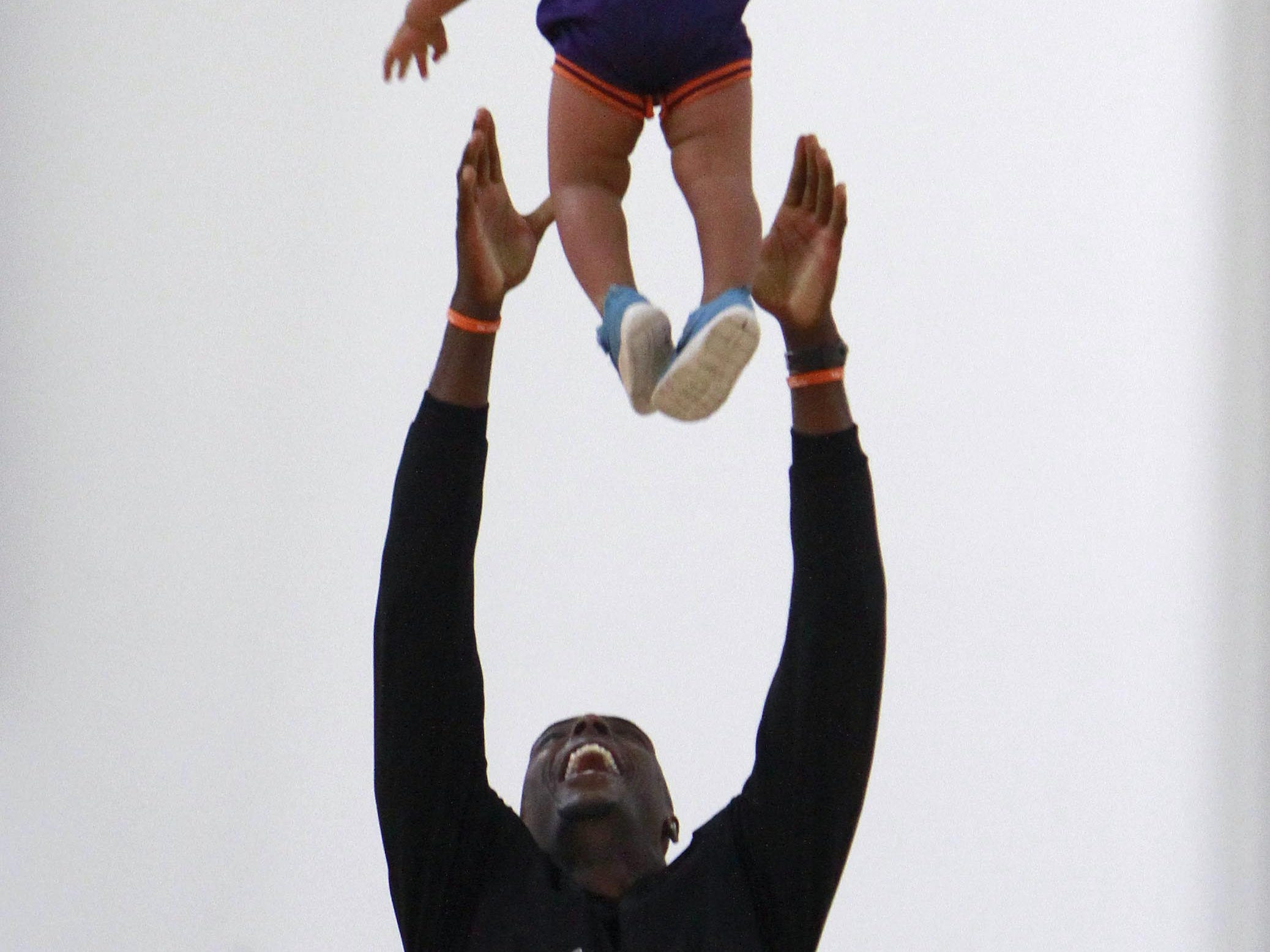 Phoenix Suns basketball player Anthony Tolliver tosses his son Isaiah, 1, into the air during his basketball camp at The Courts on Tuesday, July 22, 2014.