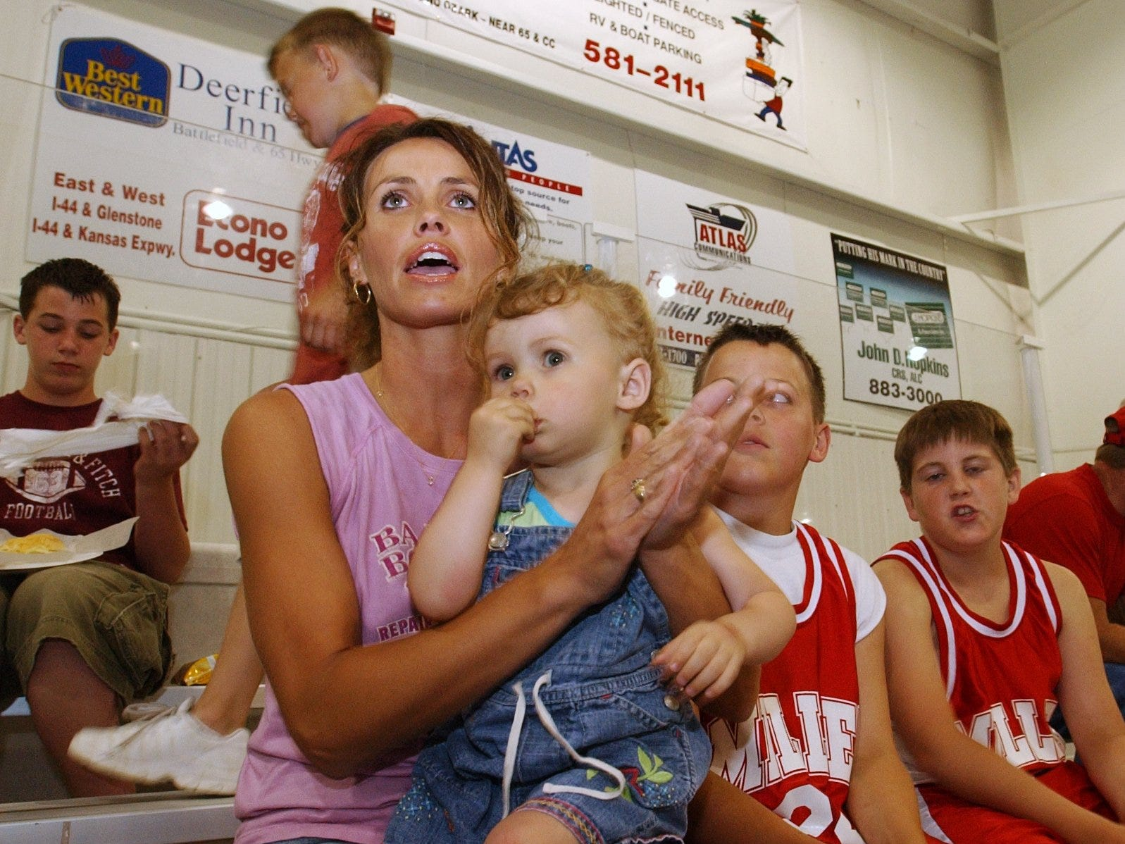 """Kyra Jack cheers on her son's basketball team while holding daughter Lexi, 2, at """"The Courts"""" in 2003."""