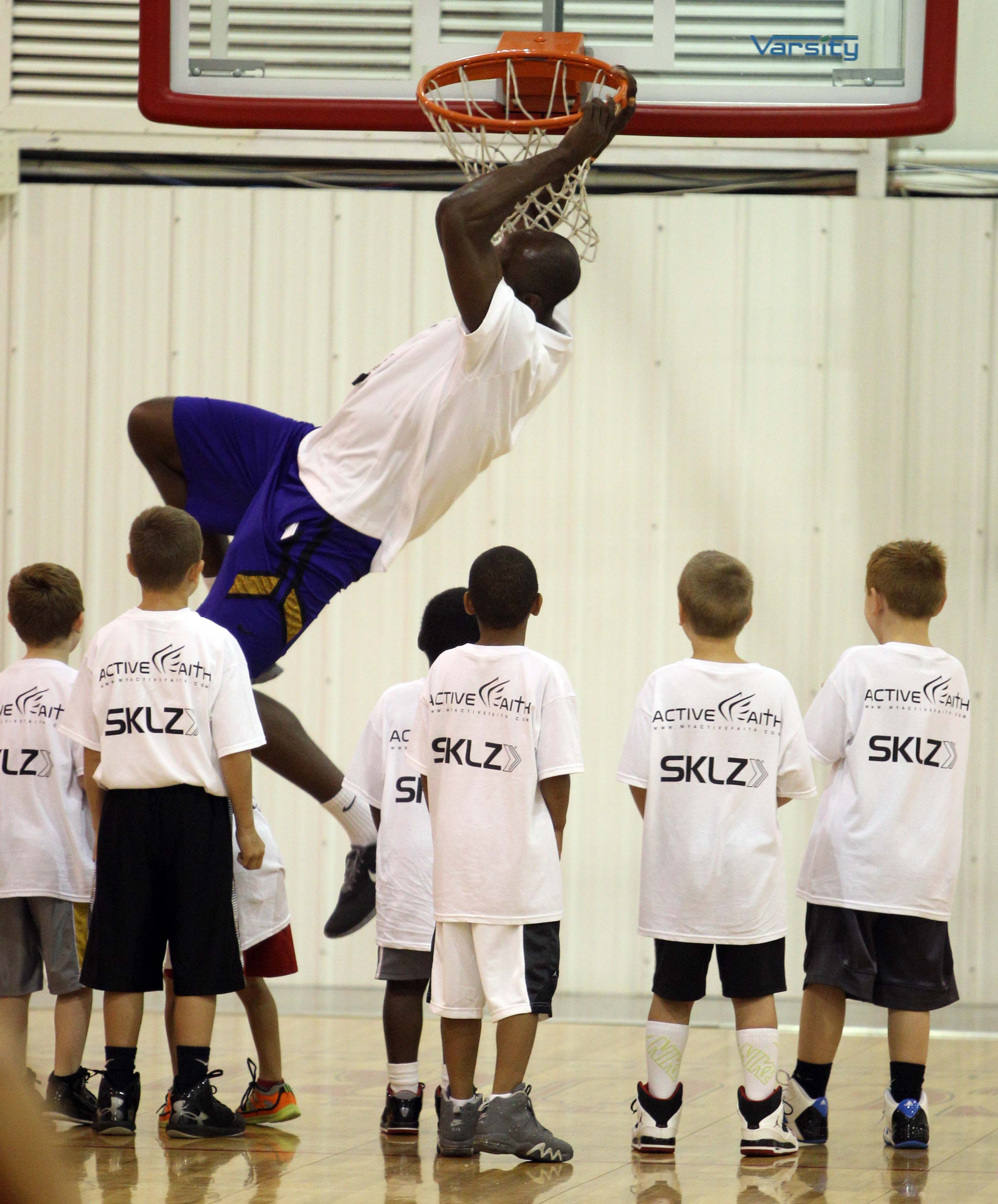 Anthony Tolliver has some fun with the youngsters at his camp at The Courts as he dunks on an 8 foot rim.