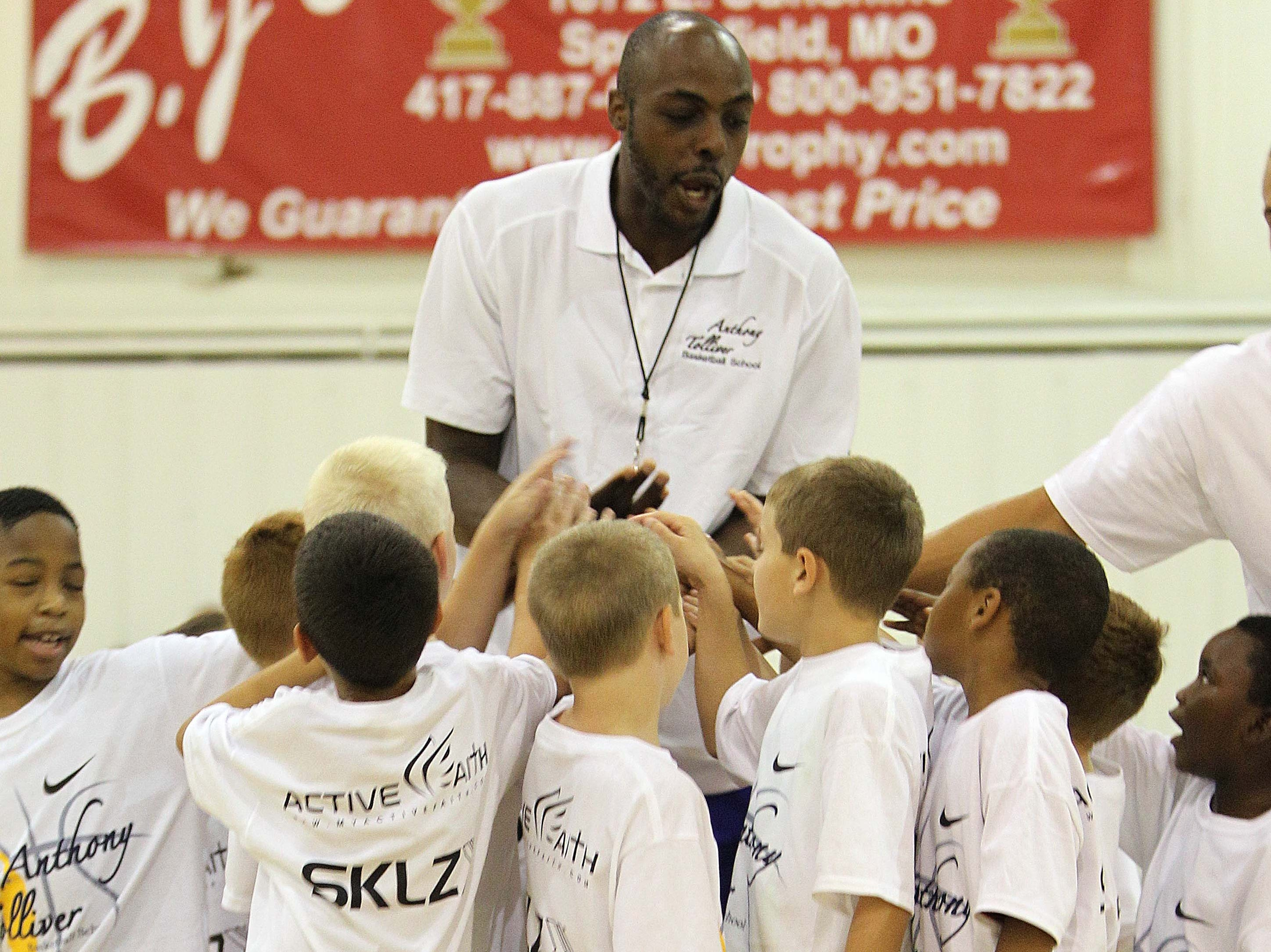 Anthony Tolliver leads a huddle of youngsters at his camp at The Courts in Springfield.