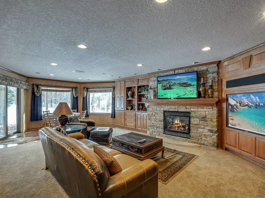 The family room centers around a long stone fireplace, surrounded by wood cabinetry and built-in screen and speaker.