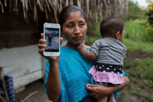 Claudia Maquin, 27, poses for a photo holding her brother-in-law's cell phone that shows an image of her daughter Jakelin Caal, in Raxruha, Guatemala, Saturday, Dec. 15, 2018. Jakelin, 7-years-old, died in a Texas hospital, two days after being taken into custody by border patrol agents in a remote stretch of New Mexico desert.