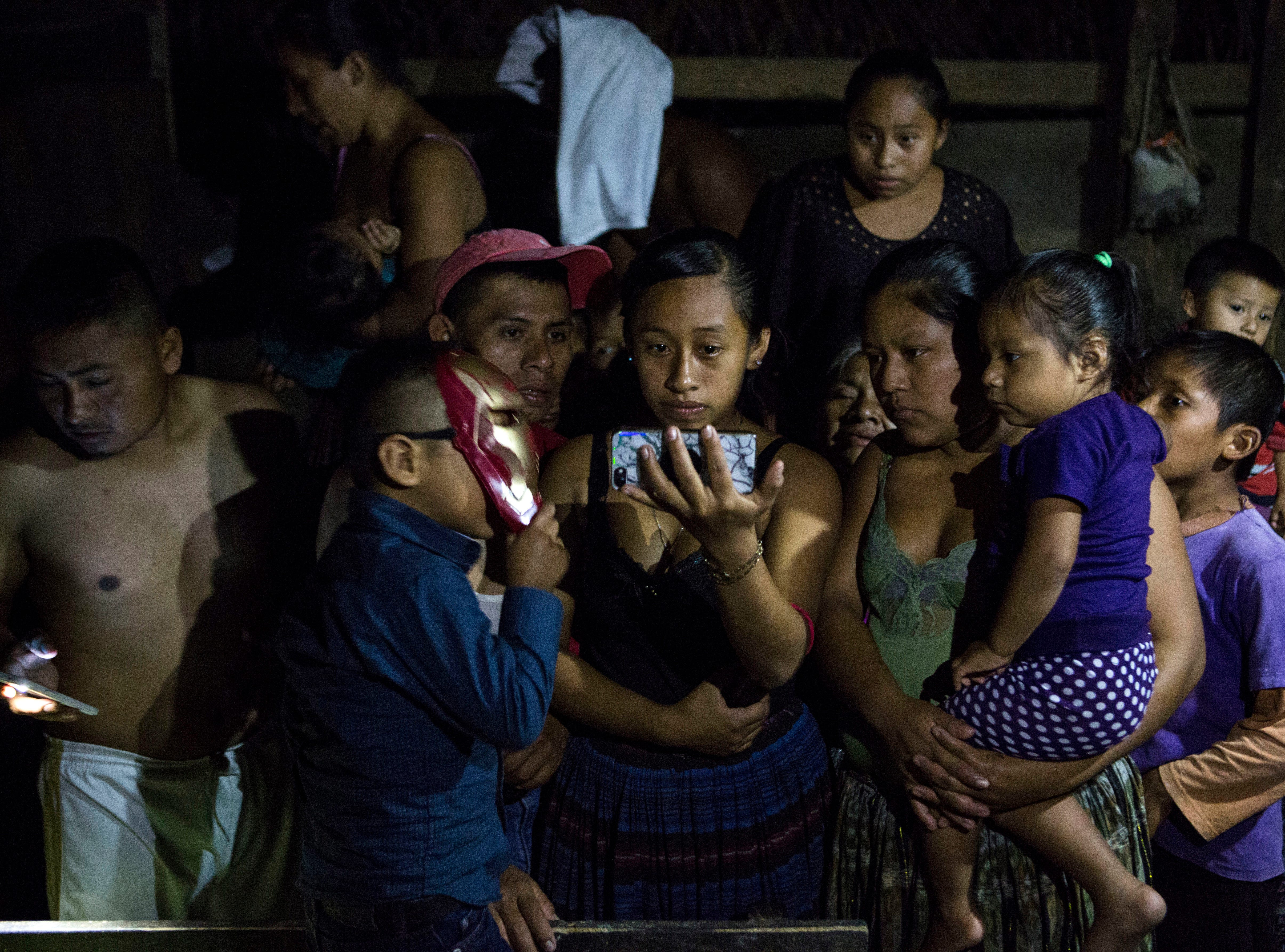 Members of the Caal Maquin family watch a video of the repatriation of Jakelin Caal Maquin's remains at Guatemala City International Airport, in San Antonio Secortez, Guatemala, Sunday, Dec. 23, 2018. The body of Caal Maquin, 7, who died while in custody of the U.S. Border Patrol, arrived in her native Guatemala on Sunday and was driven hours into the countryside to be handed over to family members for a last goodbye.
