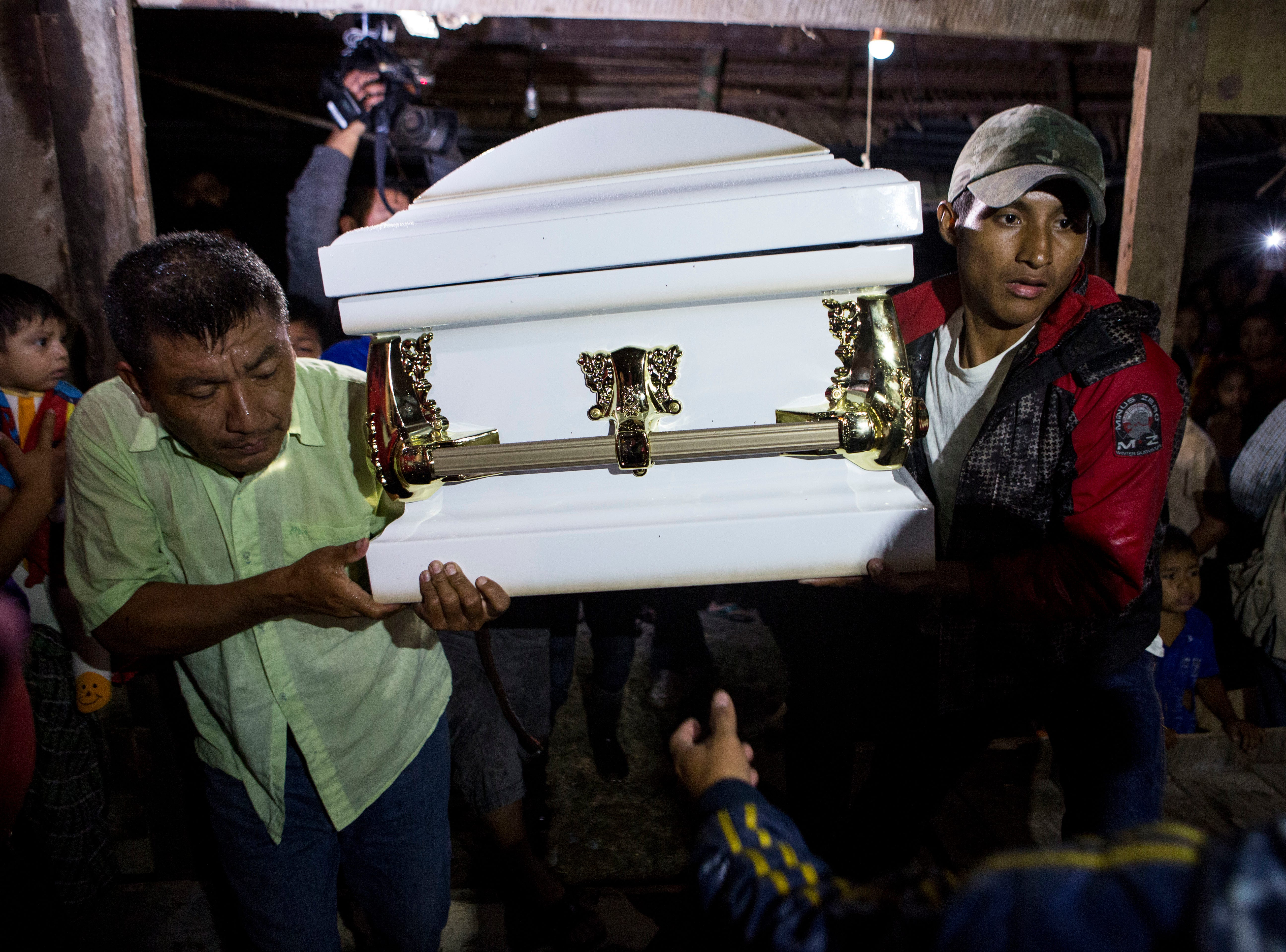 Neighbors carry the coffin that contain the remains of 7-year-old Jakelin Caal Maquin into her grandparent's home in San Antonio Secortez, Guatemala, Monday, Dec. 24, 2018. The body of a 7-year-old girl who died while in the custody of the U.S. Border Patrol was handed over to family members in her native Guatemala on Monday for a last goodbye.