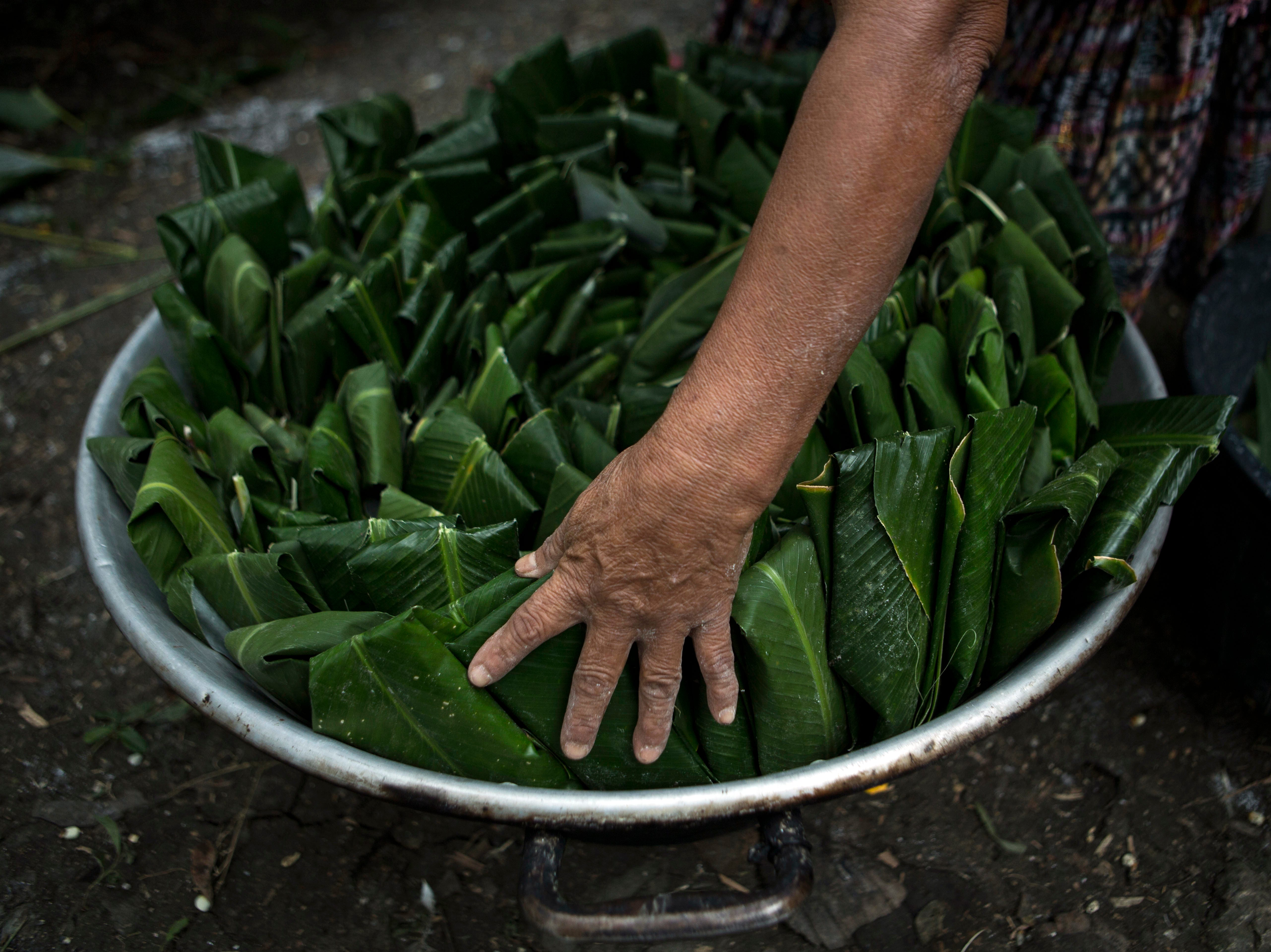 A woman cooks tamales for the relatives and neighbors who attend the funeral for Jakelin Caal Maquin, in San Antonio Secortez, Guatemala, Sunday, Dec. 23, 2018. The body of Caal Maquin, 7, who died while in custody of the U.S. Border Patrol, arrived in her native Guatemala on Sunday and was being driven hours into the countryside to be handed over to family members for a last goodbye.