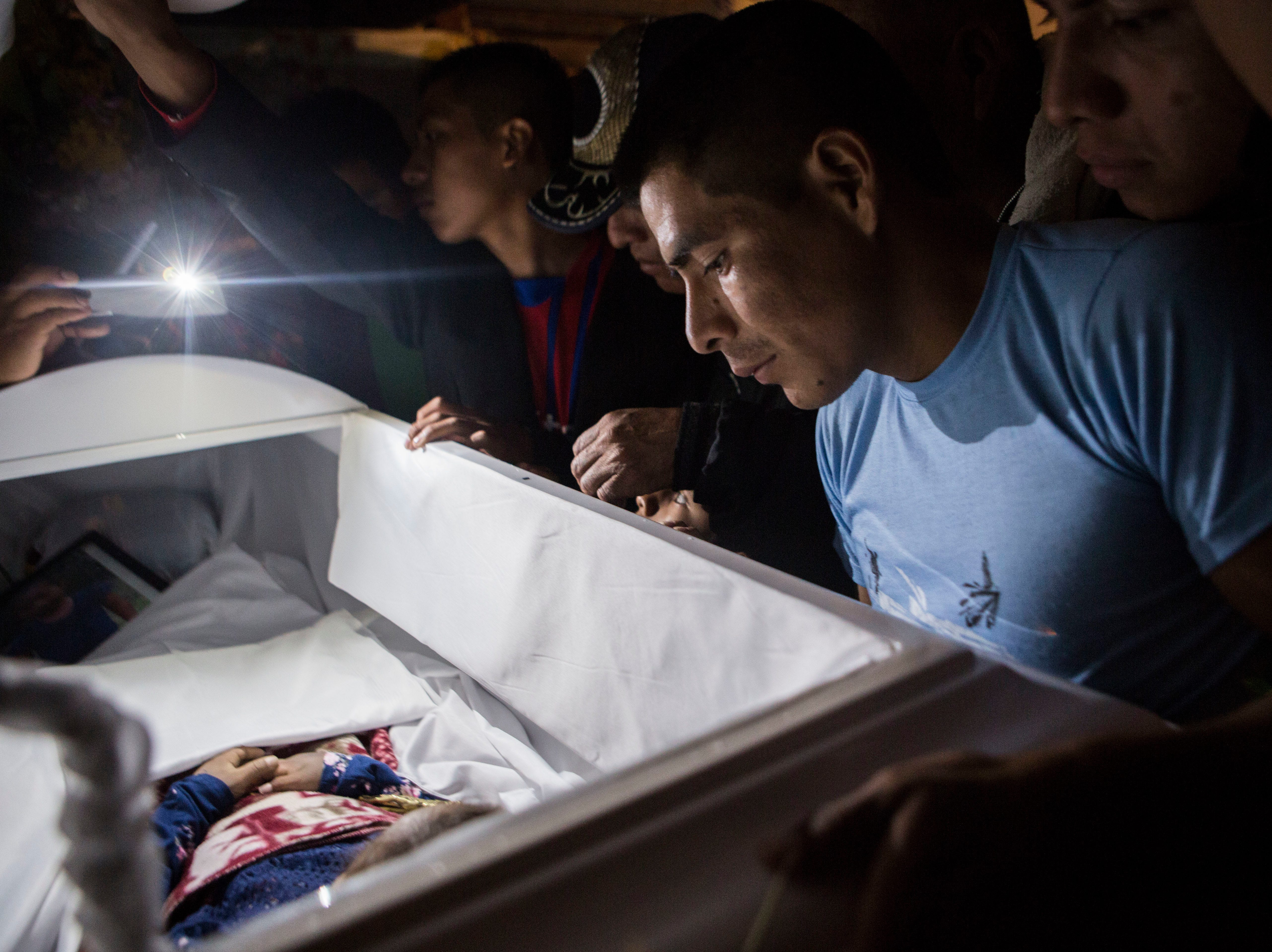 Family members pay their final respects to 7-year-old Jakelin Caal Maquin during a memorial service in her grandparent's home in San Antonio Secortez, Guatemala, Monday, Dec. 24, 2018. The body of the 7-year-old girl who died while in the custody of the U.S. Border Patrol was handed over to family members in her native Guatemala on Monday for a last goodbye.