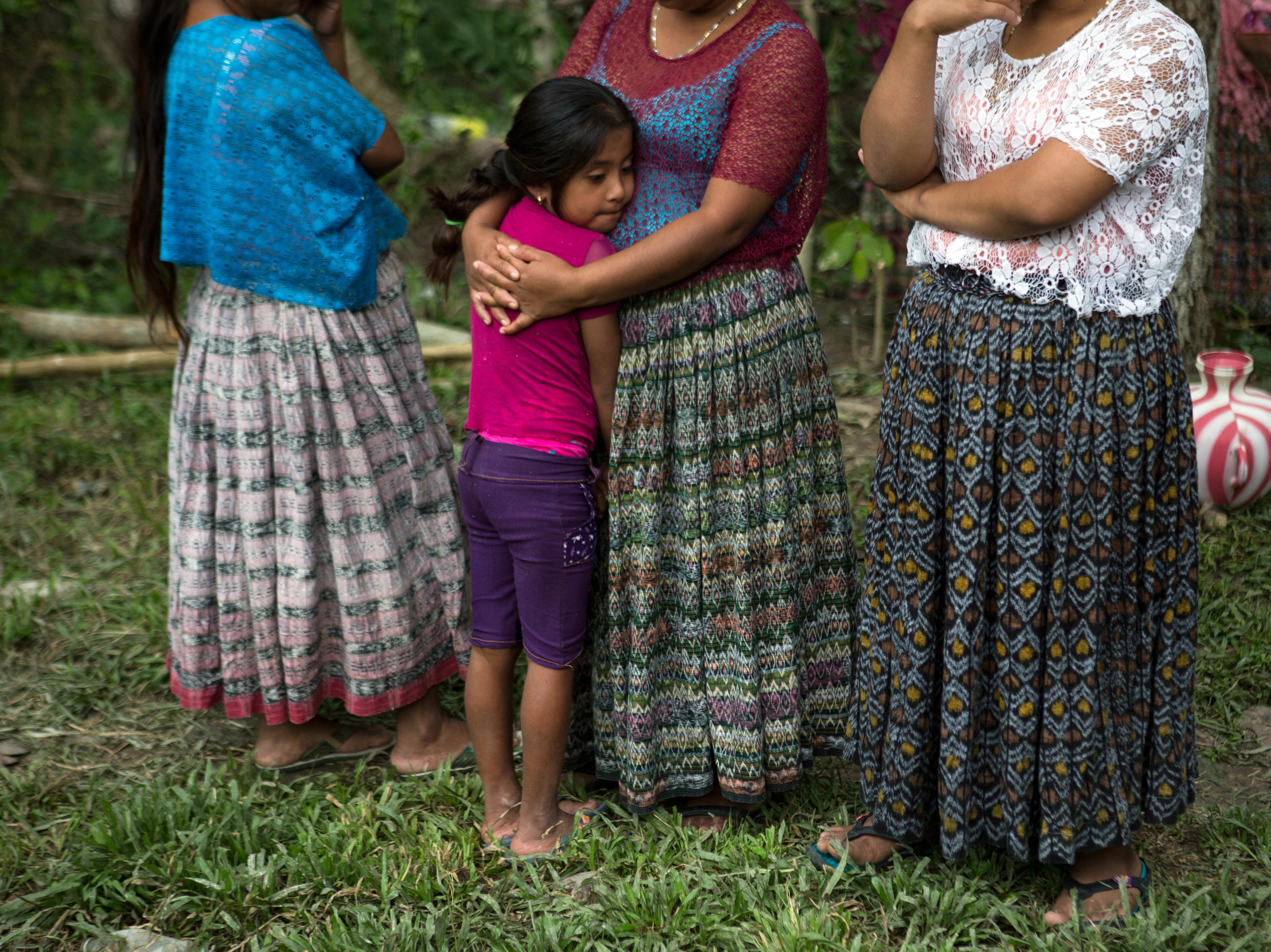A woman hugs her daughter at Jakelin Caal Maquin's grandfather's house in San Antonio Secortez, Guatemala, Sunday, Dec. 23, 2018. The body of Caal Maquin, 7, who died while in custody of the U.S. Border Patrol, arrived in her native Guatemala on Sunday and was being driven hours into the countryside to be handed over to family members for a last goodbye.