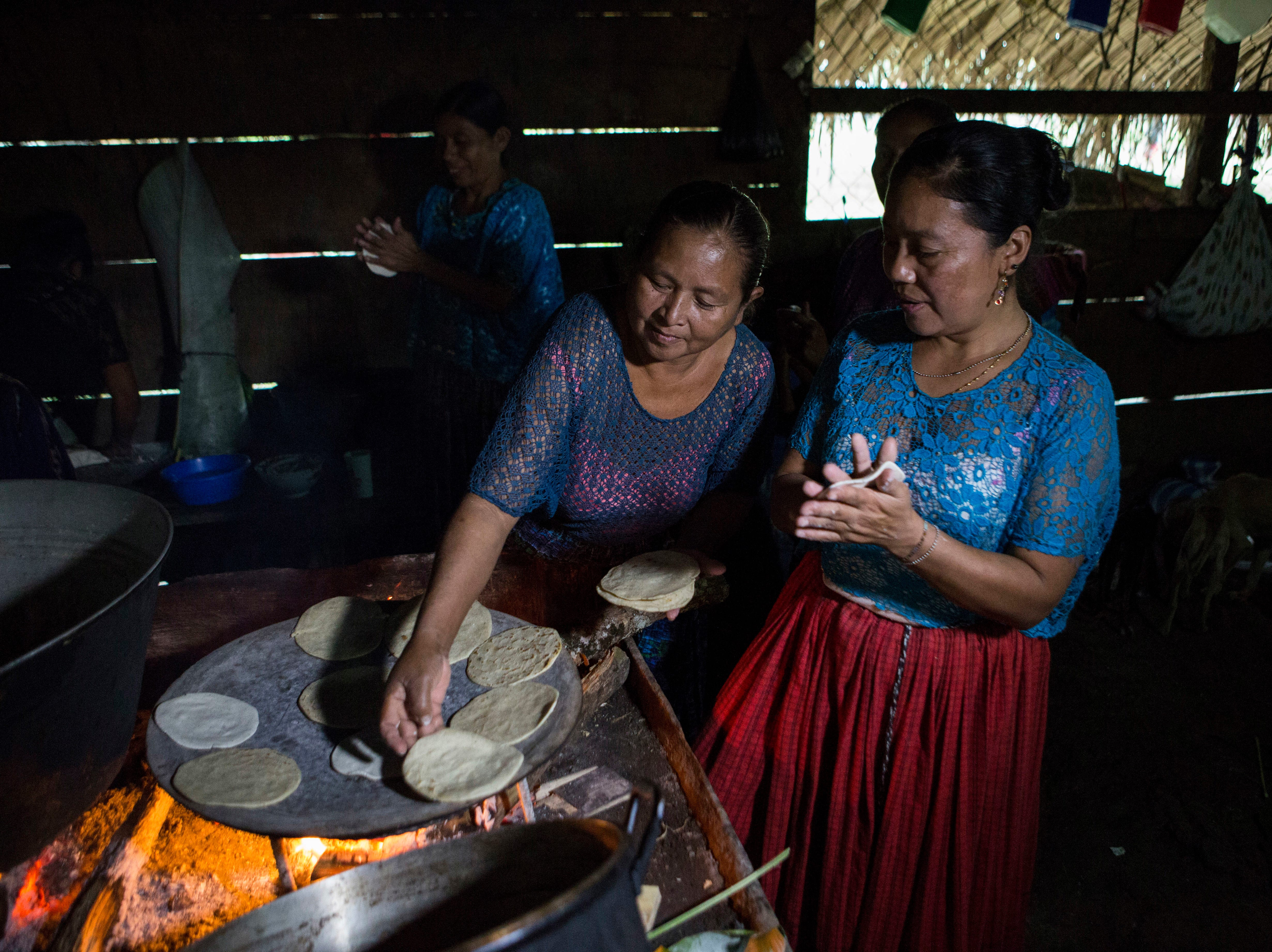 Women make corn tortillas at Jakelin Caal Maquin grandfather's house in San Antonio Secortez, Guatemala, Sunday, Dec. 23, 2018. The body of Caal Maquin, 7, who died while in custody of the U.S. Border Patrol, arrived in her native Guatemala on Sunday and was being driven hours into the countryside to be handed over to family members for a last goodbye.