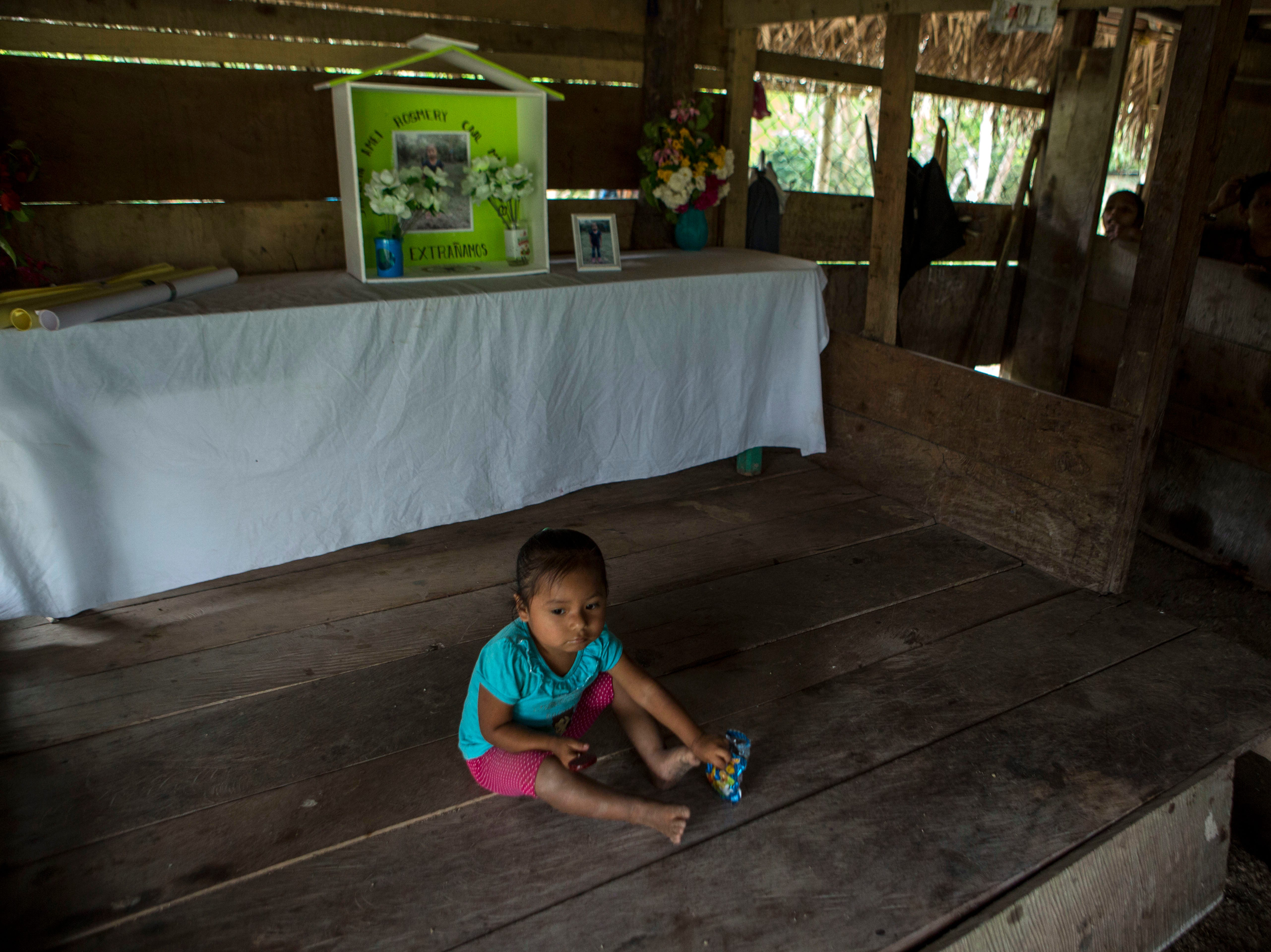 A girl sits in front of a memorial to Jakelin Caal Maquin at the house of Caal Maquin's grandfather, in San Antonio Secortez, Guatemala, Sunday, Dec. 23, 2018. The body of Caal Maquin, 7, who died while in custody of the U.S. Border Patrol, arrived in her native Guatemala on Sunday and was being driven hours into the countryside to be handed over to family members for a last goodbye.