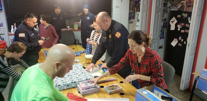 Members of the Vineland Fire Department wrap Christmas gifts Sunday night for a family in need.