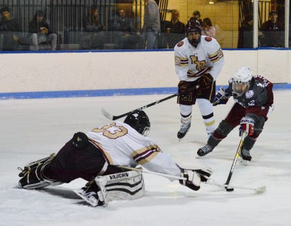 Iona Prep goalie Ricky Selwa and Fordham Prep forward Will Rice extend themselves in hopes of reaching a loose puck on the doorstep in the first period Sunday.