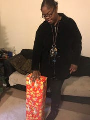 Cachet Parker shows off the Christmas present waiting for the 4-year-old girl shot inside her apartment Sunday night.