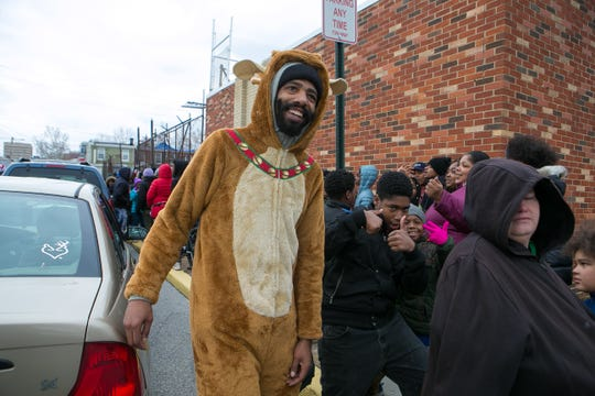 """Thousands of children and families wait in line at the parking lot of Christian Growth Ministries as LaDaye """"Cooley"""" Johnson, a Wilmington East Side native gives out the more than 10,000 toys he's collected to give back to a community that raised him."""