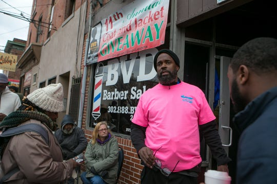 Terrone Warren, owner of Black Visionary Designers (BVD) Barber Salon, gives instructions to the people lined outside his business as he holds his 11th annual coat and jacket giveaway on Christmas eve.