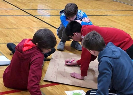 Wisconsin Rapids Area Middle School wrestlers work on a sign for their brat fry earlier this month.