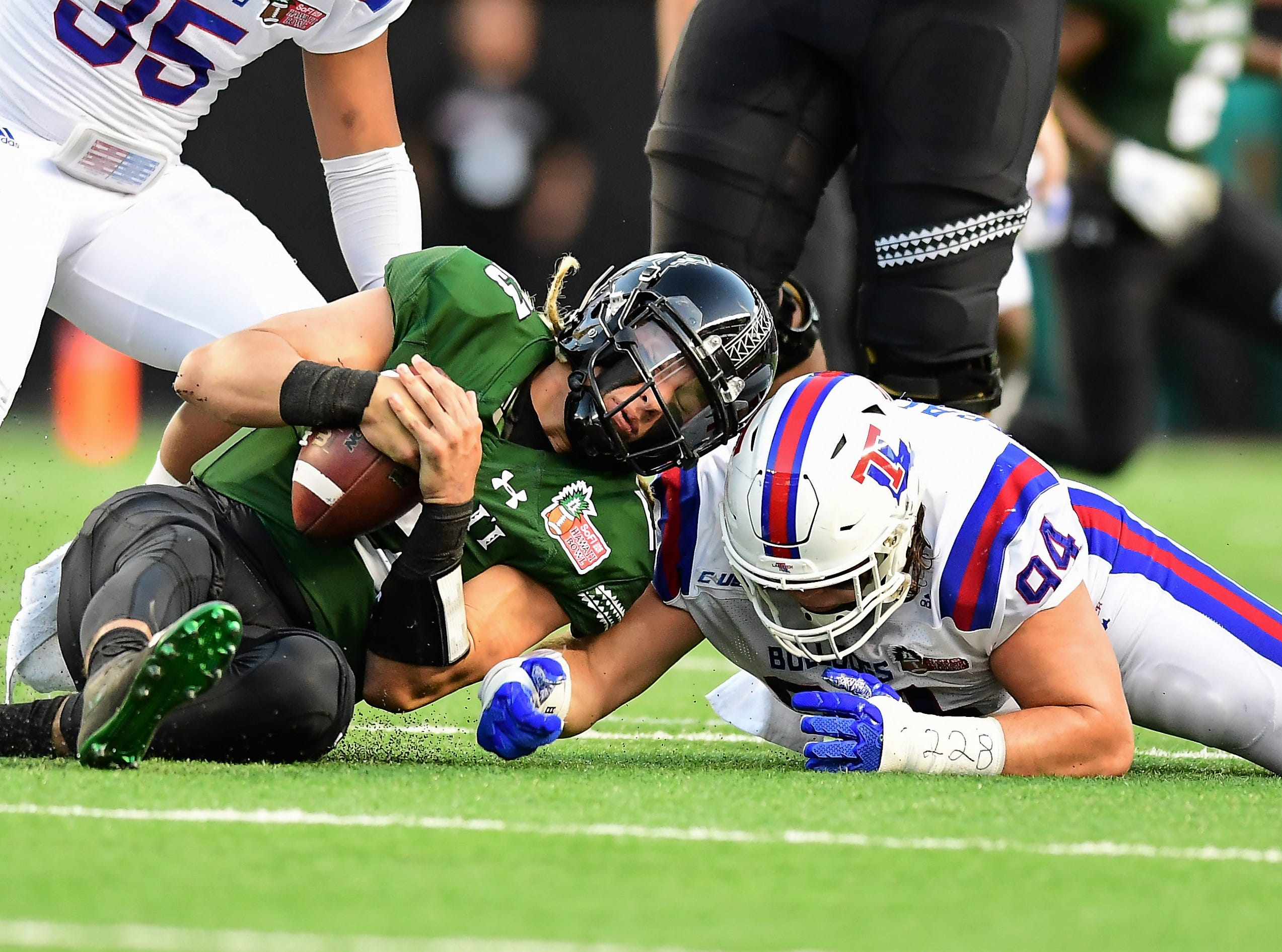 Hawaii Warriors quarterback Cole McDonald (13) fights for a loose ball against Louisiana Tech Bulldogs defensive tackle Jordan Bradford (94) during the first quarter of the Hawaii Bowl.