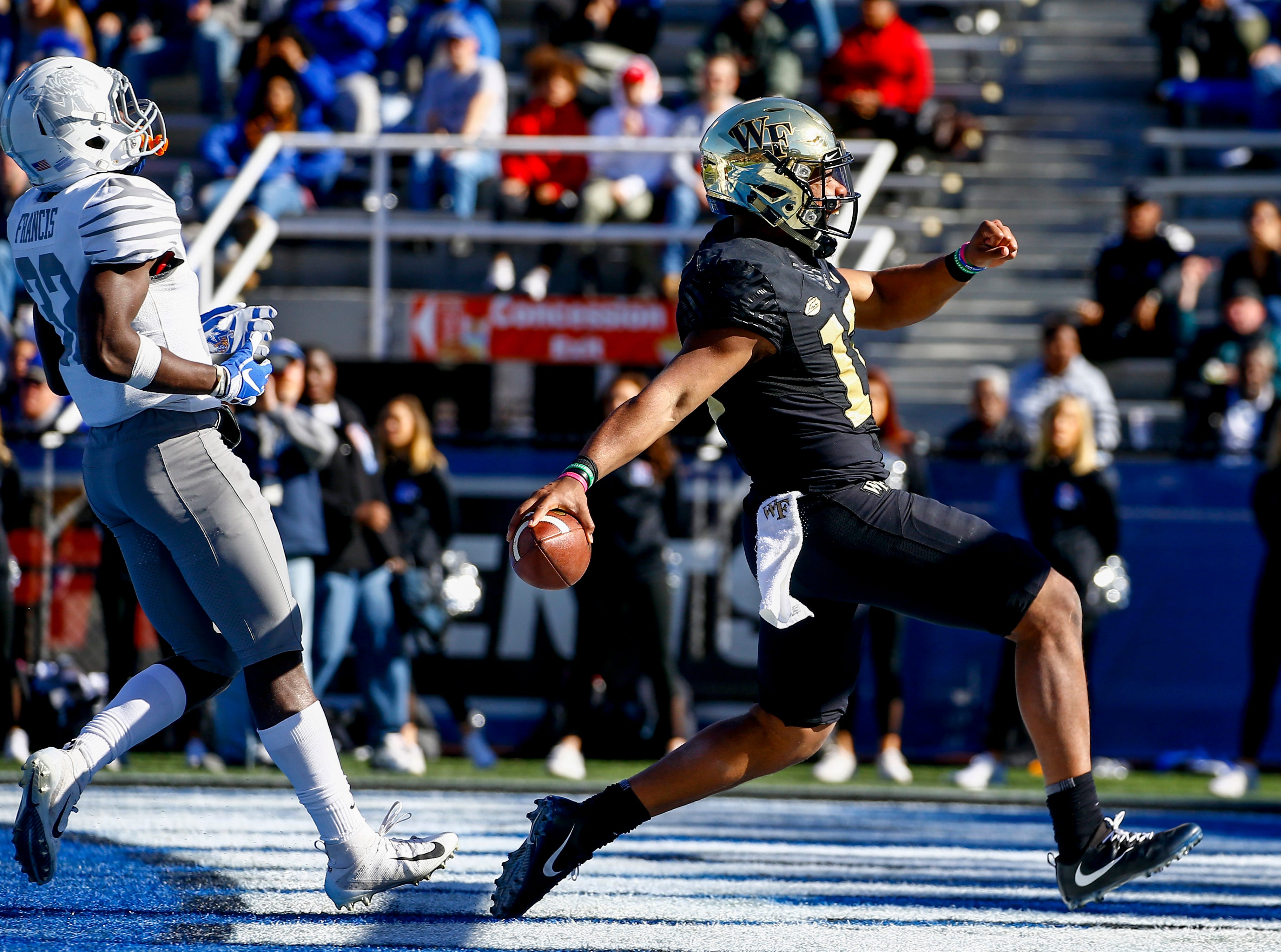 Wake Forest Demon Deacons quarterback Jamie Newman (12) carries the ball in for a touchdown as Memphis Tigers defensive back Jacobi Francis (32) defends during the first half of the Birmingham Bowl.