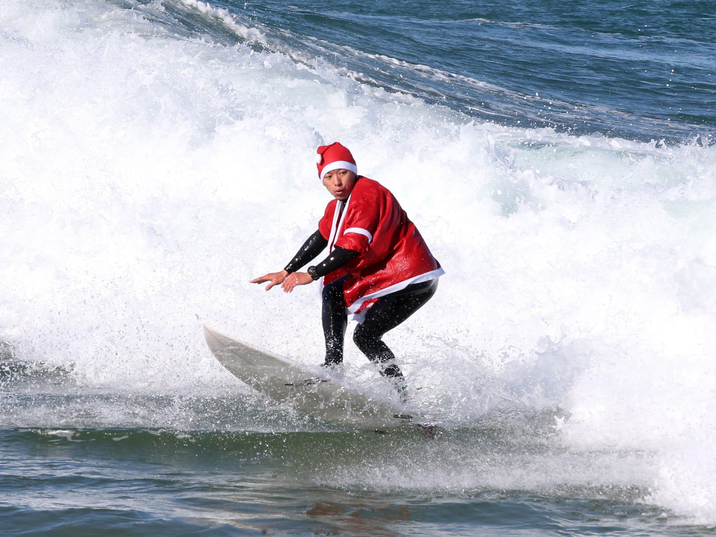 epa07247251 A surfer dressed as Santa Claus rides a wave near Pohang, 375 kilometers southeast of Seoul, South Korea, 24 December 2018.  EPA-EFE/YONHAP SOUTH KOREA OUT